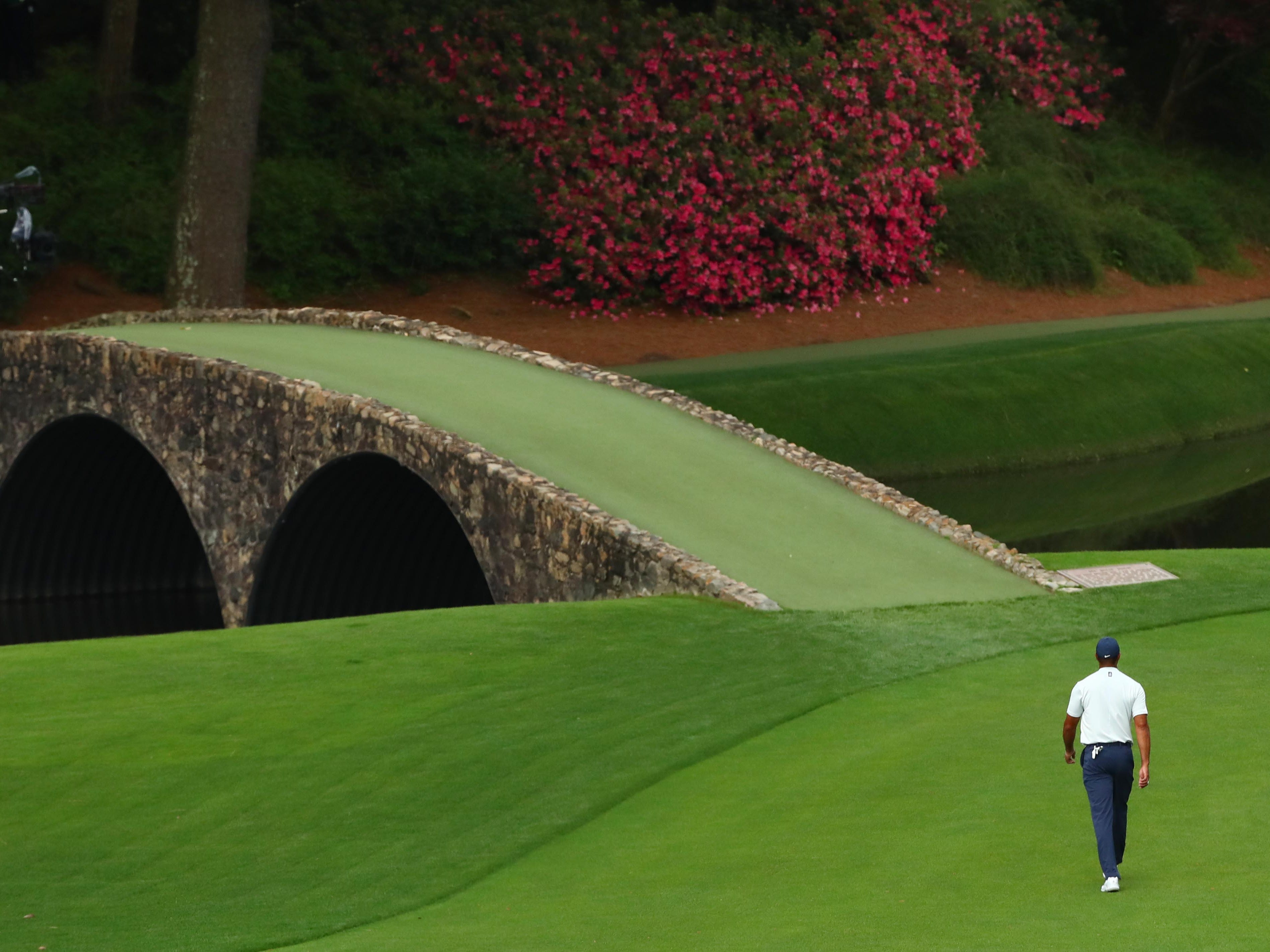 Tiger Woods walks across the Hogan Bridge to mark his ball on the 12th green after play is suspended during the second round of the Masters.