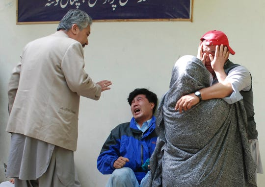 Relatives of the victims of the explosion comfort each other on Friday, April 12, 2019, in front of a morgue in Quetta, Pakistan. A powerful bomb struck an open-air market in the southwestern city of Quetta on Friday, police and hospital officials said.
