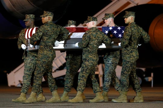A U.S. Marine Corps carry team moves a transfer case containing the remains of Staff Sgt. Christopher Slutman, Thursday, April 11, 2019, at Dover Air Force Base, Del. According to the Department of Defense, Slutman, of Newark, Del., was among three American service members killed by a roadside bomb on Monday, April 8, near Bagram Airfield in Afghanistan.