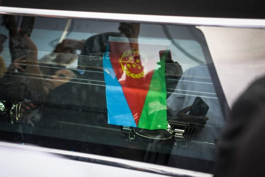 The National flag of Eritrea lays over the casket of Nipsey Hussle as it passes The Marathon Store on the corner of Crenshaw and Slauson on April 11, 2019.