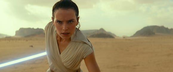 "Rey (Daisy Ridley) swings her lightsaber yet again in ""Star Wars: The Rise of Skywalker."""