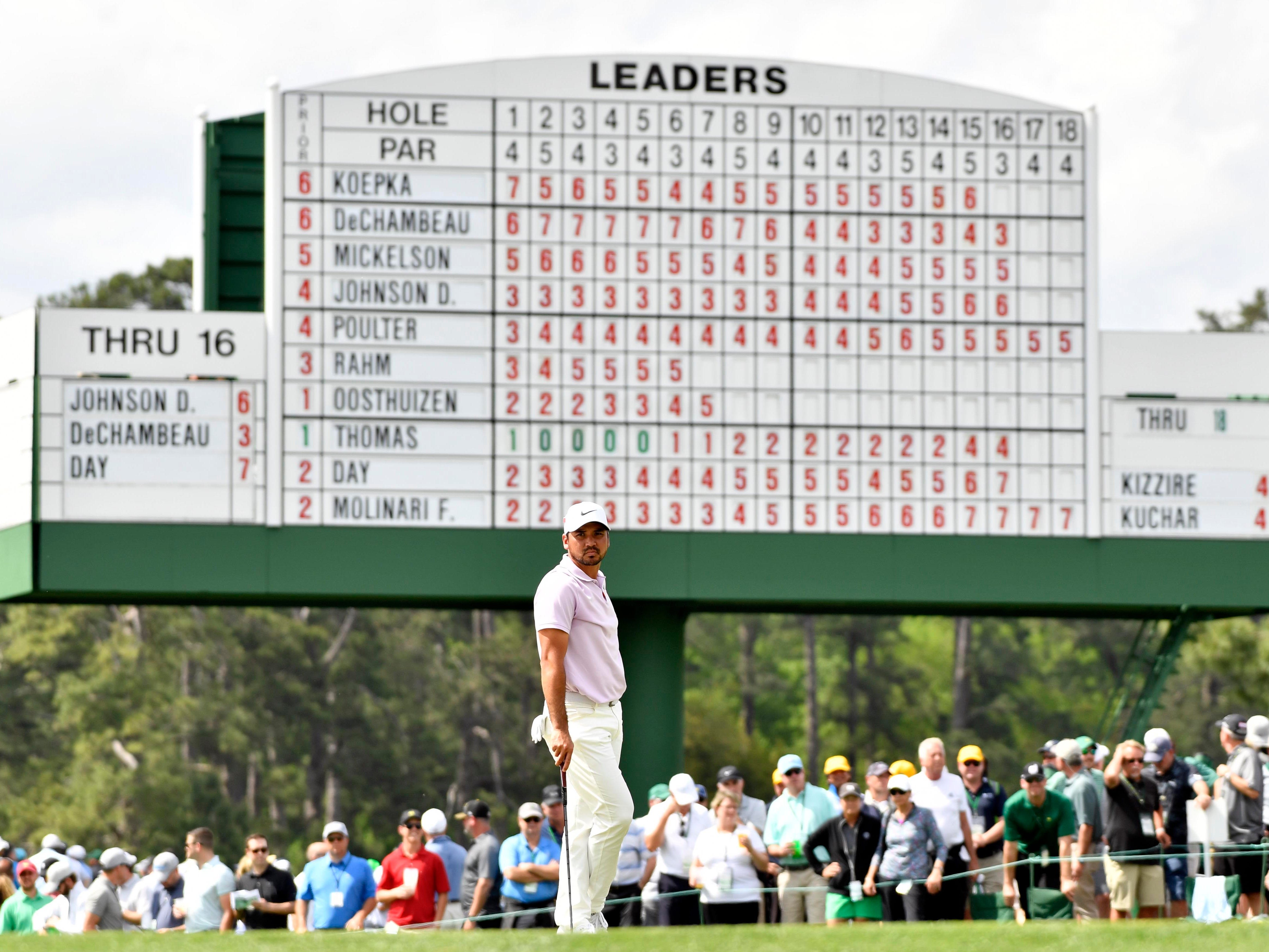 Jason Day stands under the leaderboard on the 17th green during the second round of the Masters.