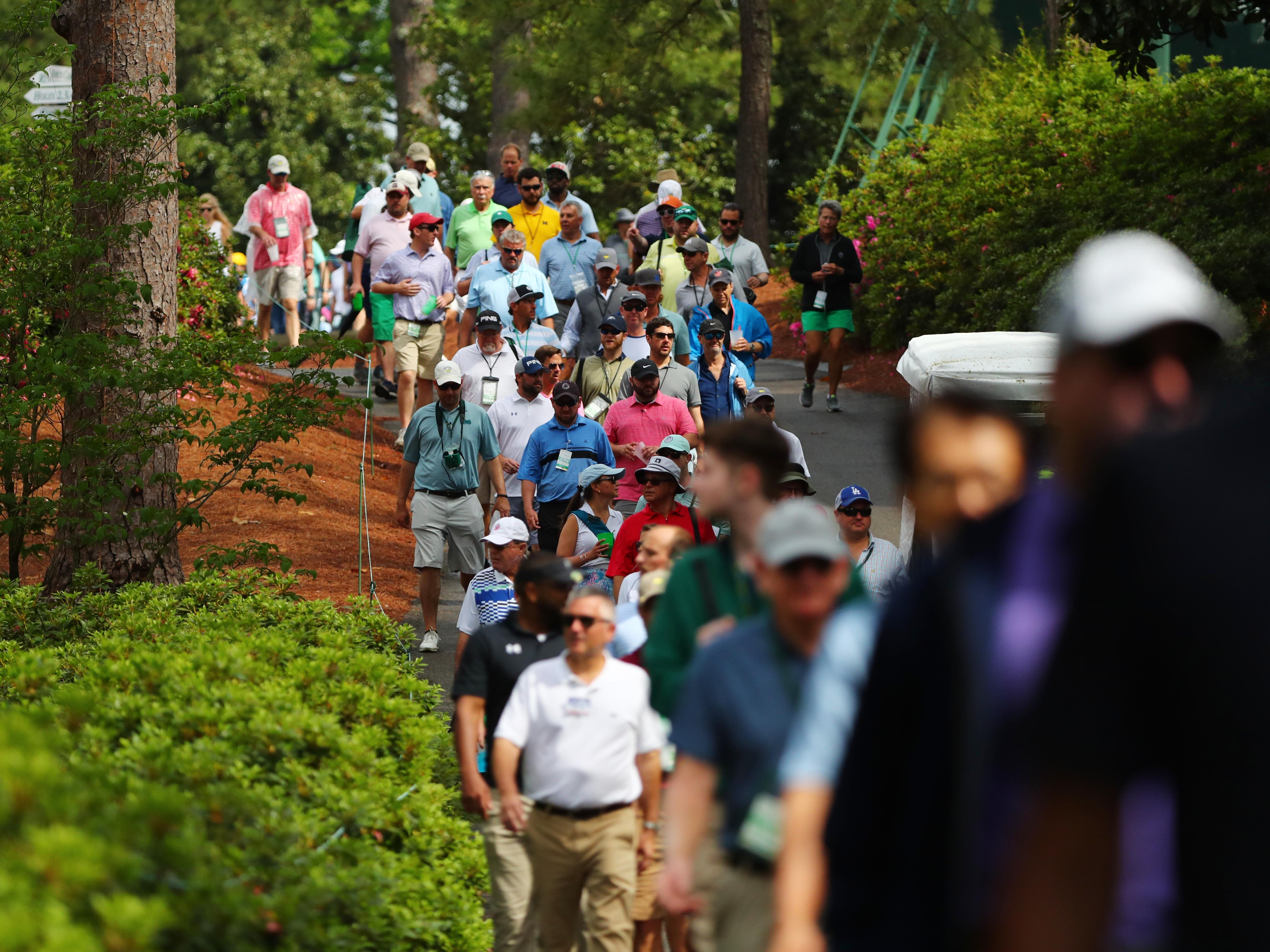 Patrons walk along the second hole during the second round of the Masters.