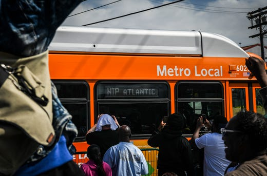 """Supporters cheer as a Los Angeles Metro bus displays """"NIP"""" on the side of the bus on the corner of Crenshaw and Slauson on April 11, 2019."""