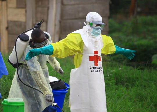 "In this Sunday, Sept 9, 2018 file photo, a health worker sprays disinfectant on his colleague after working at an Ebola treatment center in Beni, eastern Congo.  Top Red Cross official Emanuele Capobianco said Friday April 12, 2019, that he's ""more concerned than I have ever been"" about the possible regional spread of the Ebola virus in Congo after a recent spike in cases."