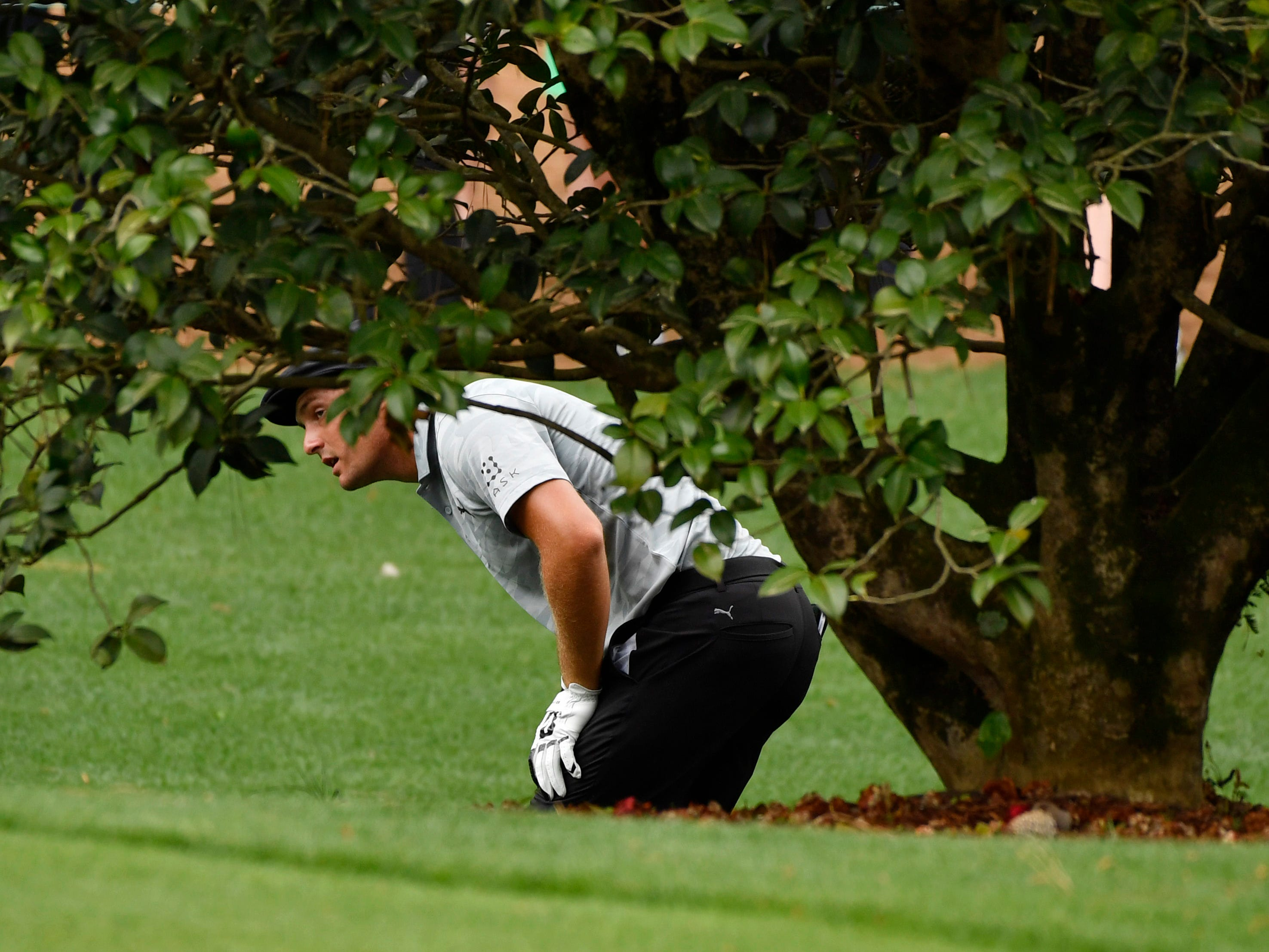 Bryson DeChambeau looks for his ball in the rough on the 10th hole during the second round of the Masters.