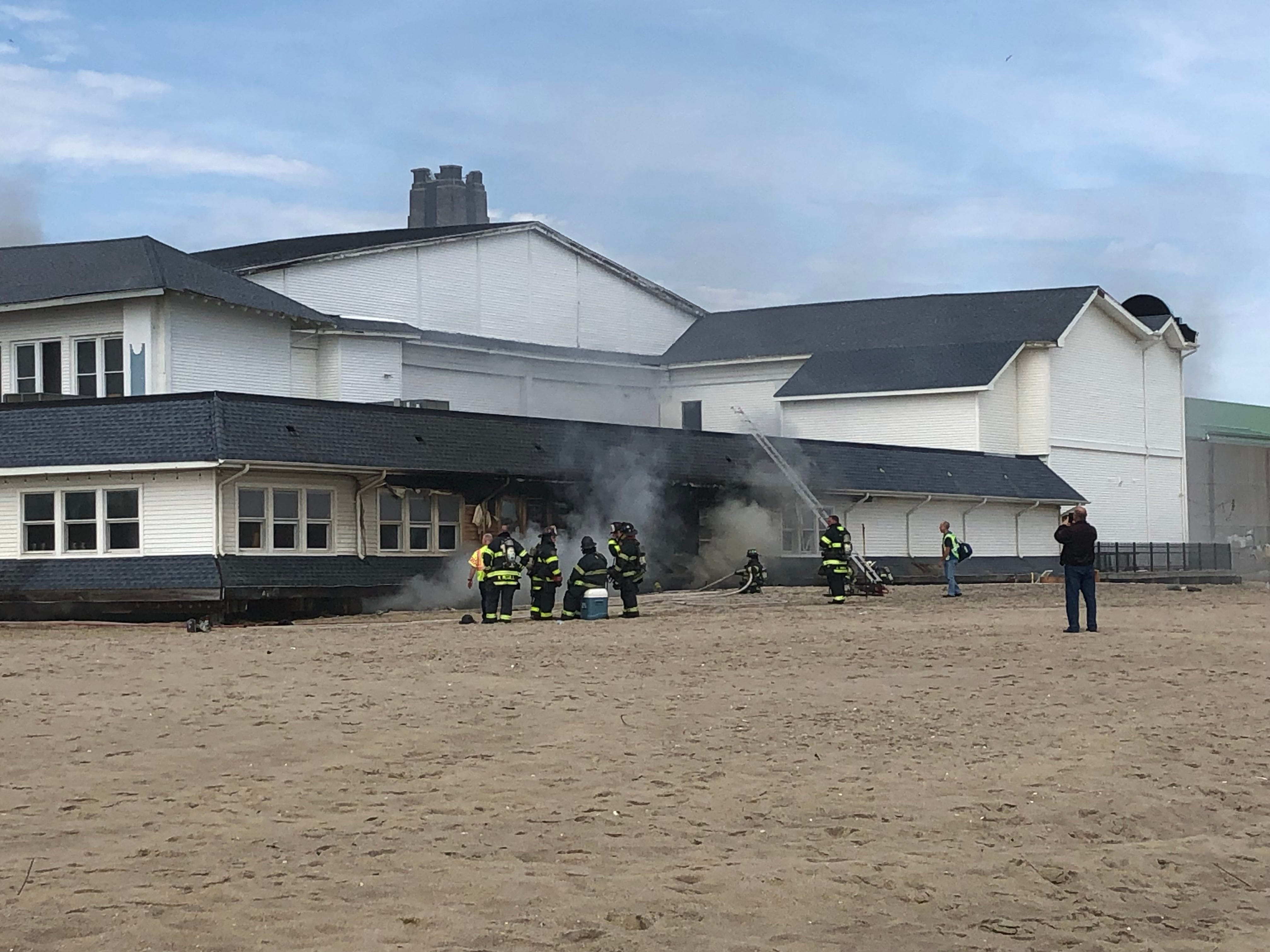 Firefighters battle at fire that broke out at Dunes Boardwalk Cafe and spread to an adjoining strip of stores.