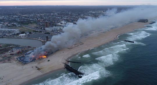 Firefighters continue to battle a fire on the north end of the Ocean Grove boardwalk into the evening Saturday, April 13, 2019.