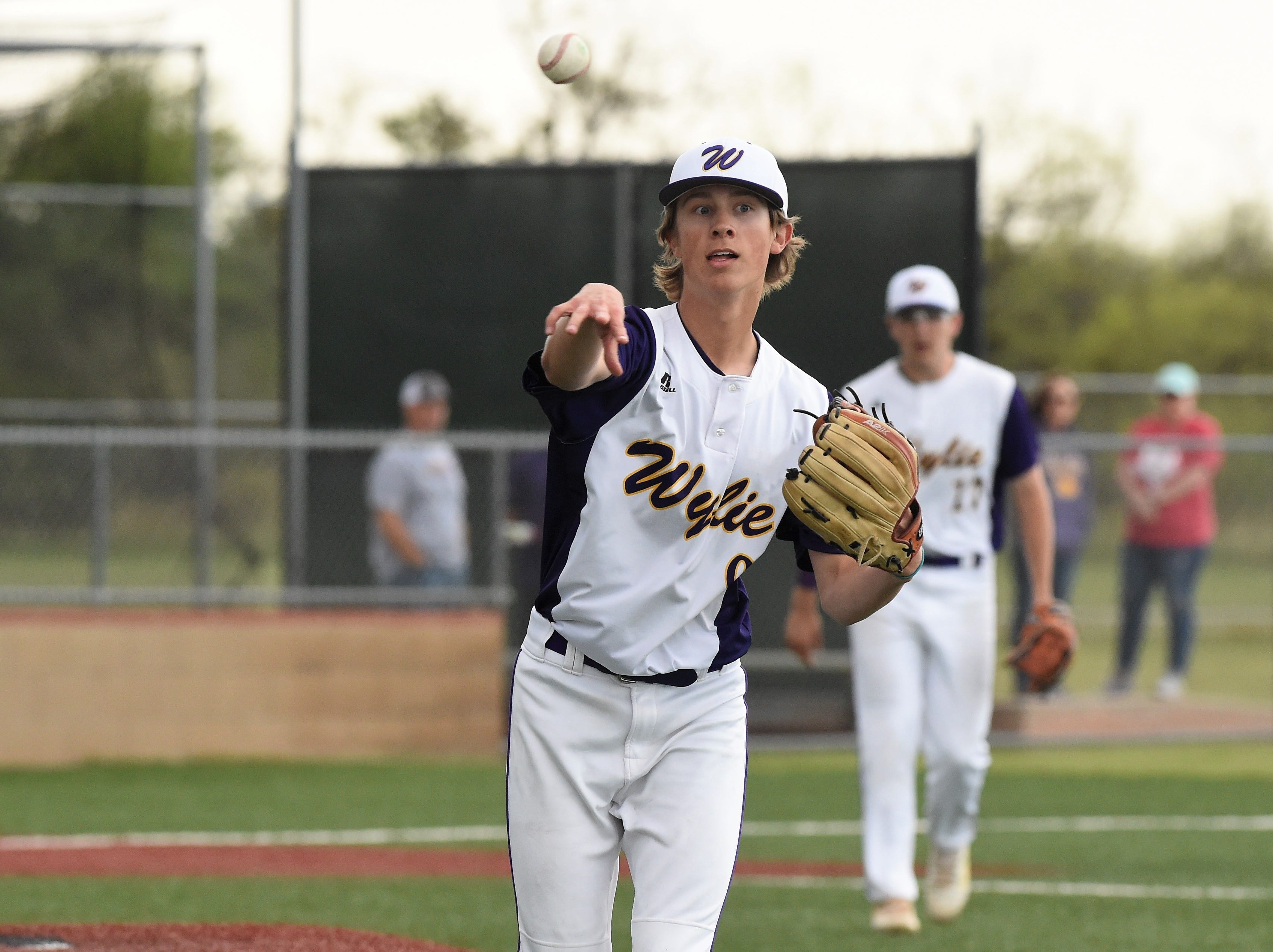 Wylie pitcher Brooks Gay (9) tosses the ball to first for an out against Cooper at Bulldog Field on Friday, April 12, 2019. Gay earned the win, allowing an unearned run in six innings.