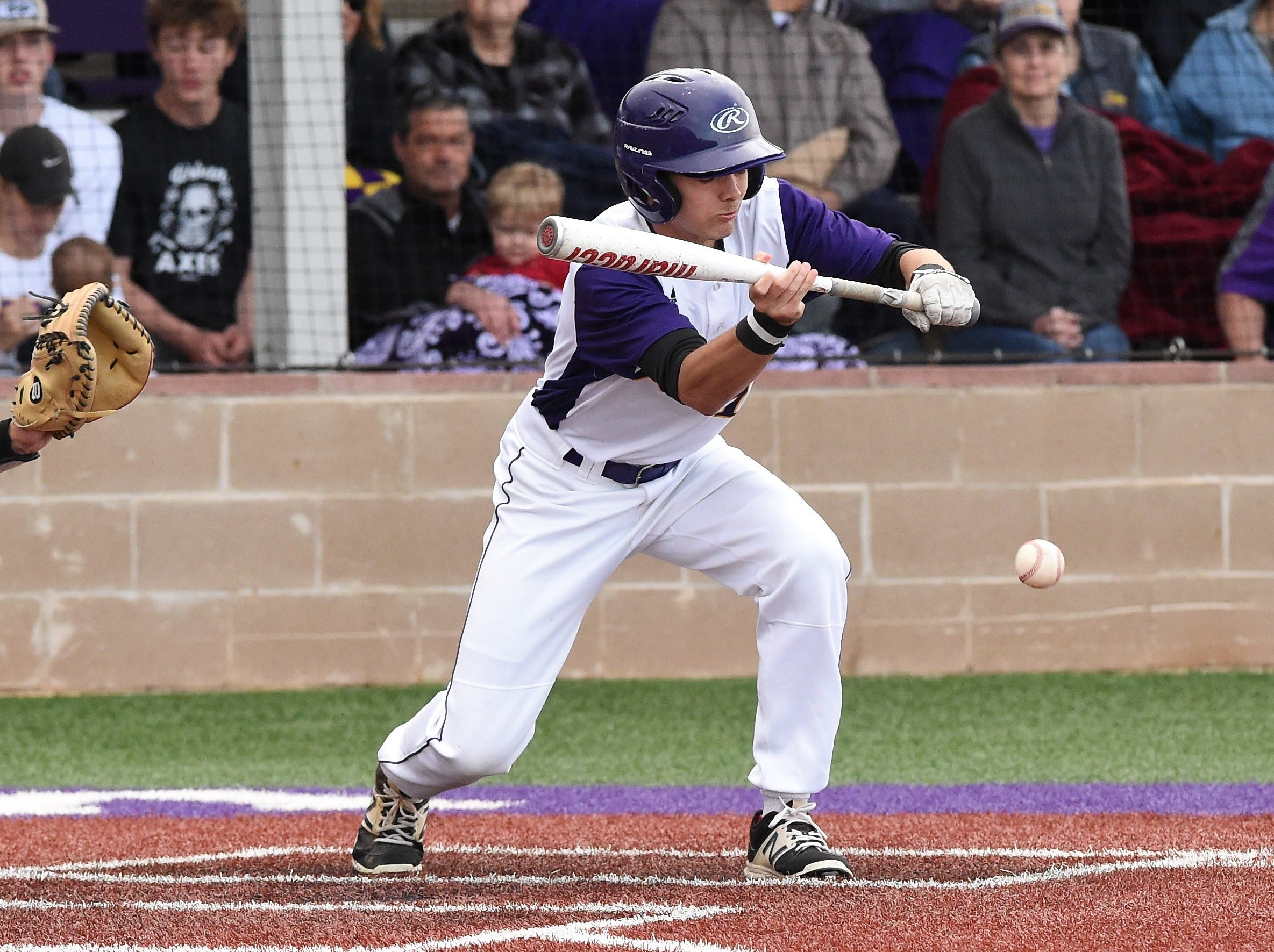 Wylie's Brandon Sanders (19) puts down a successful bunt against Cooper at Bulldog Field on Friday, April 12, 2019. The Bulldogs held on for a 4-3 win.