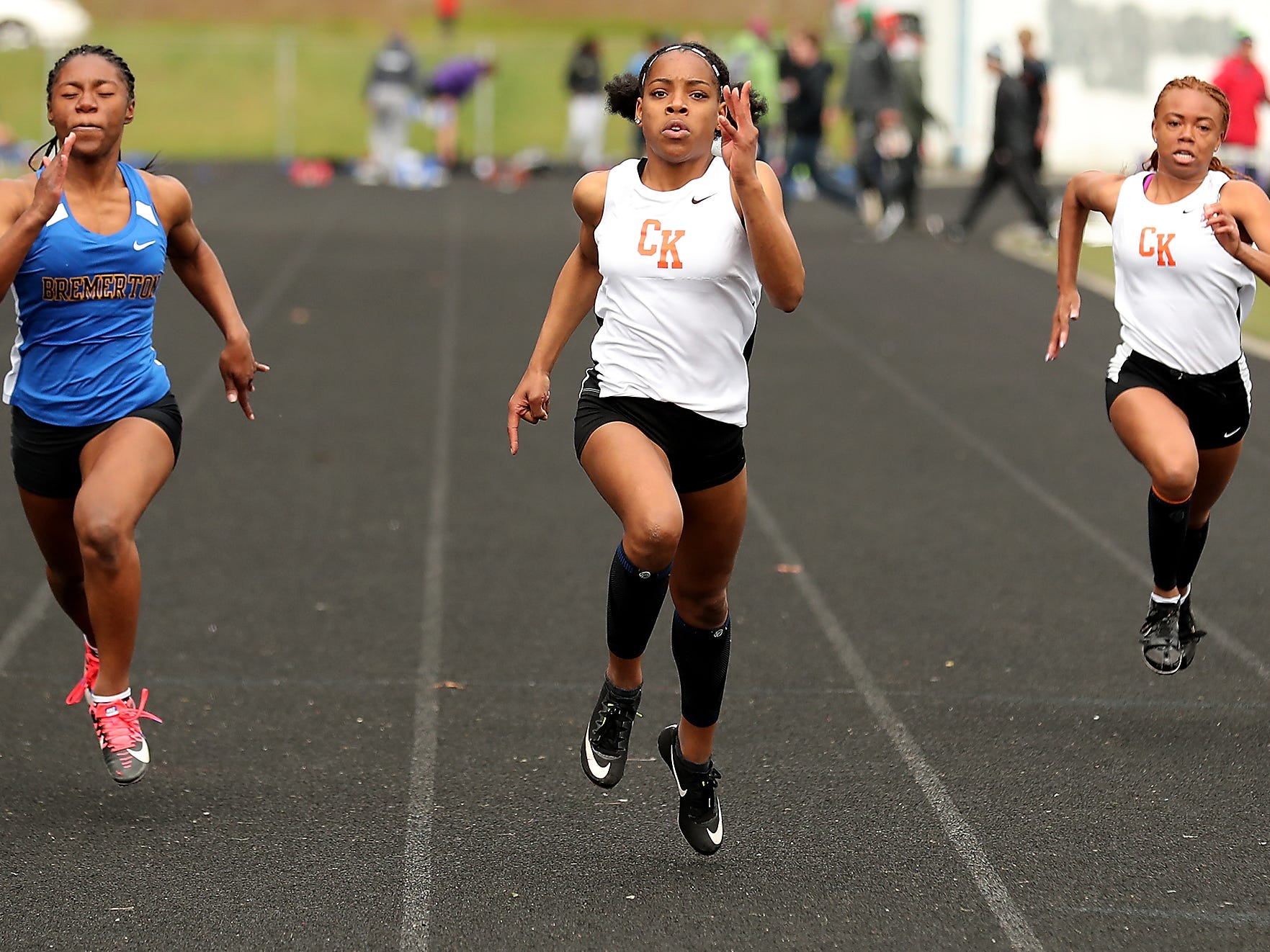 Central Kitsap's Kymeal Gaulden (center) sprints for a first place finish in the 100 Meter Dash ahead of Bremerton's T'Caela Wilcher (left) and Central Kitsap's A'Naiyah Davis (right) during the Lil' Norway Invitational at North Kitsap High School in Poulsbo on Saturday, April13, 2019.
