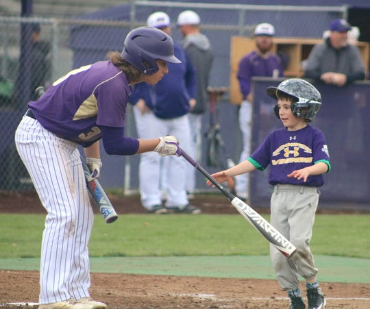 North Kitsap's Josh Fisher hands a bat to Vikings bat boy Daniel Prince during Friday's game against Port Angeles in Poulsbo.