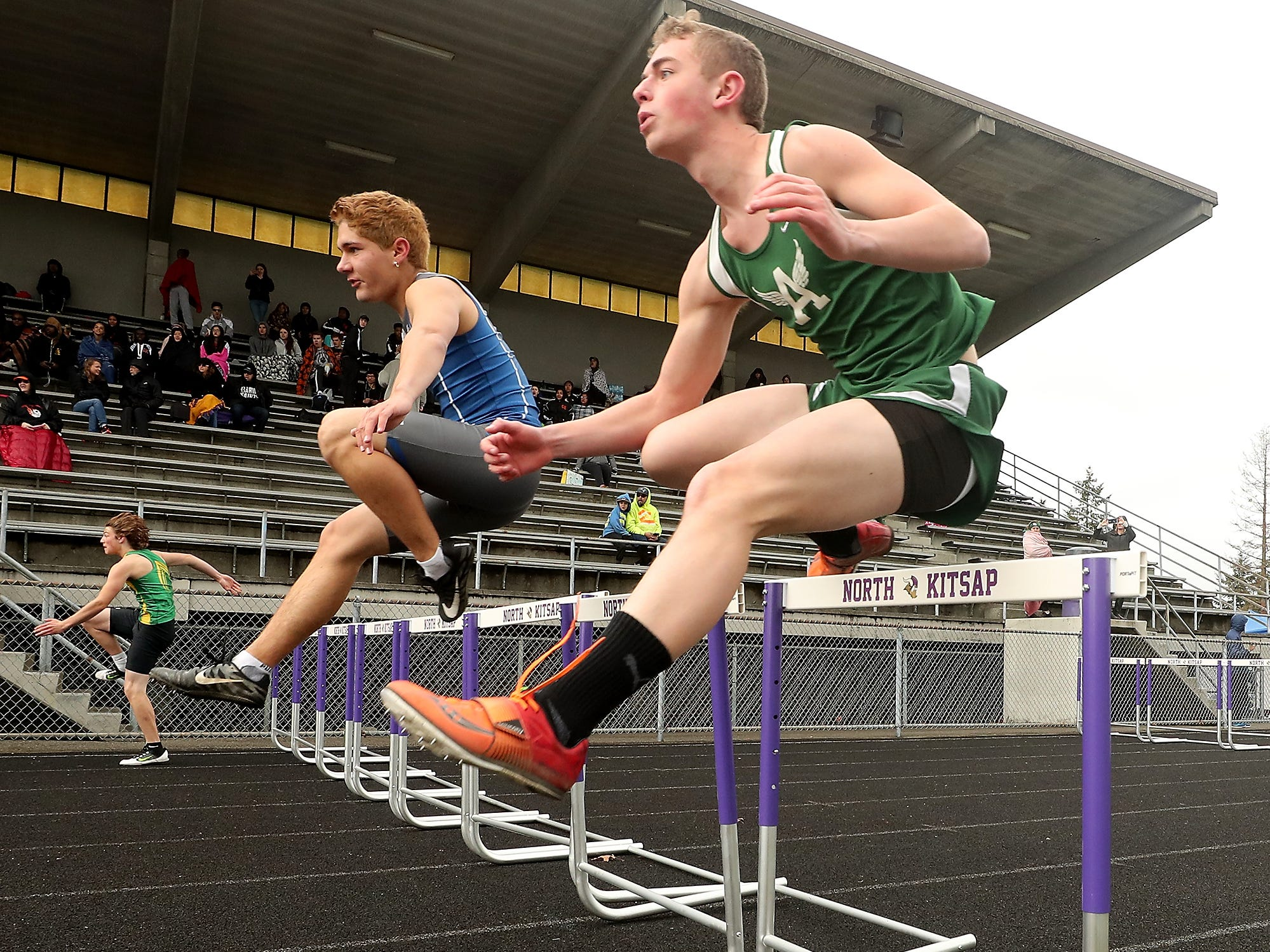 Olympic's Zachary Wyant and Port Angeles's Caleb Flodstrom (right) clear a set of hurdles during the Lil' Norway Invitational at North Kitsap High School in Poulsbo on Saturday, April13, 2019.