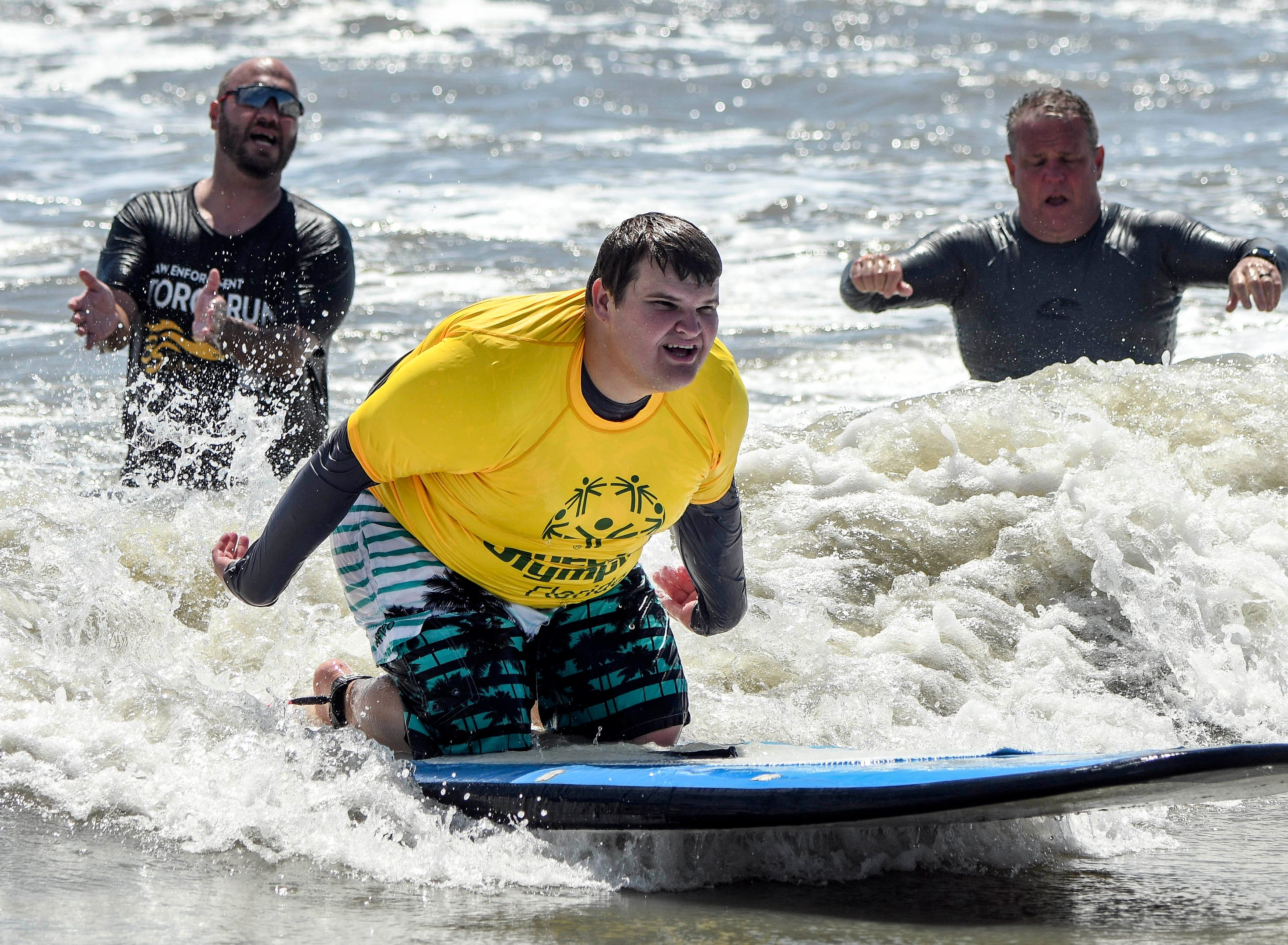 Jacob Nehus is encouraged by volunteers as he participates in the Special Olympics spring surfing festival at Shepard Park.
