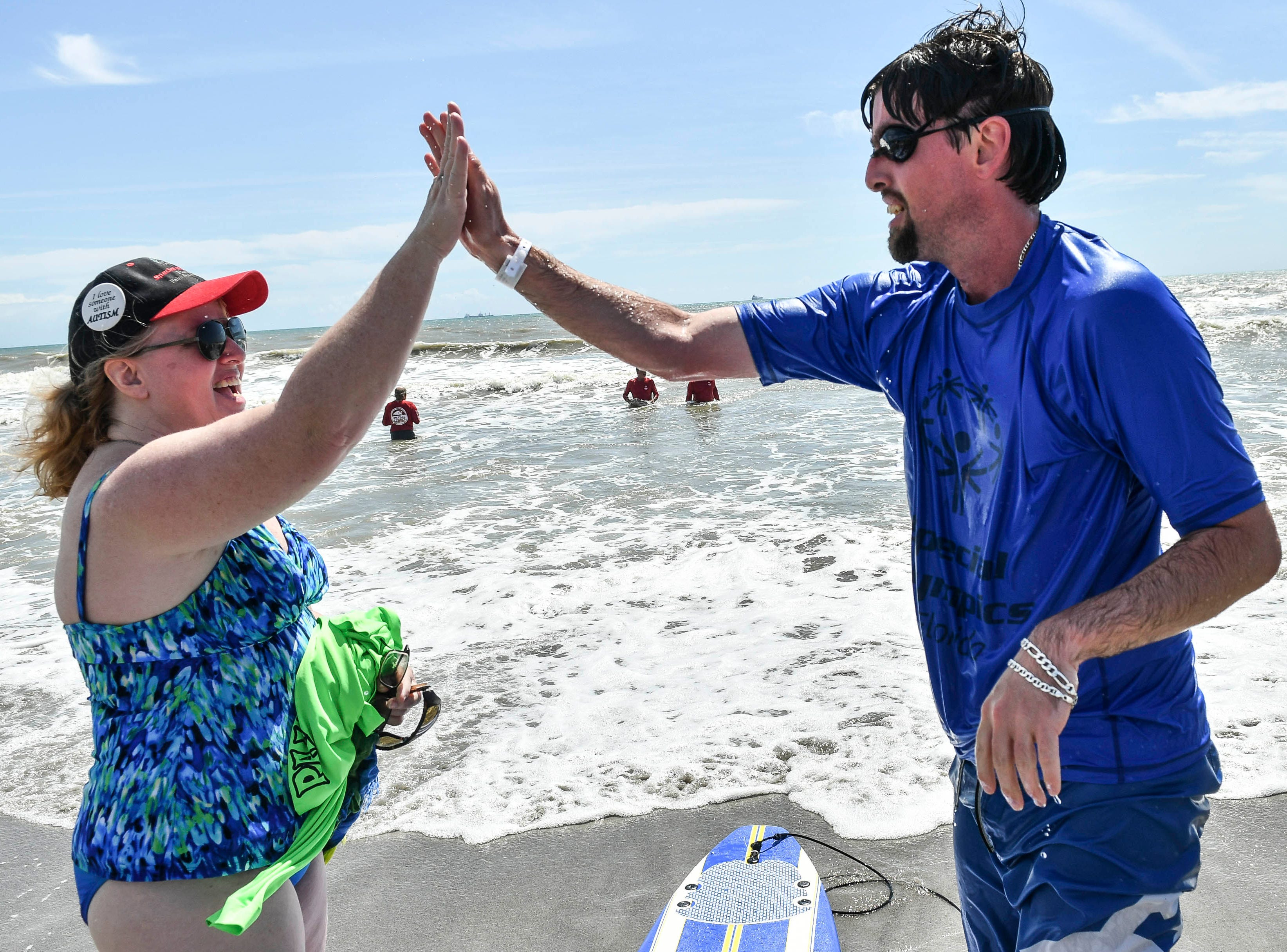 Peggy Hutchison-Padron high fives her son Bryan Padron after he finished competing in the Special Olympic spring surfing festival at Shepard Park.