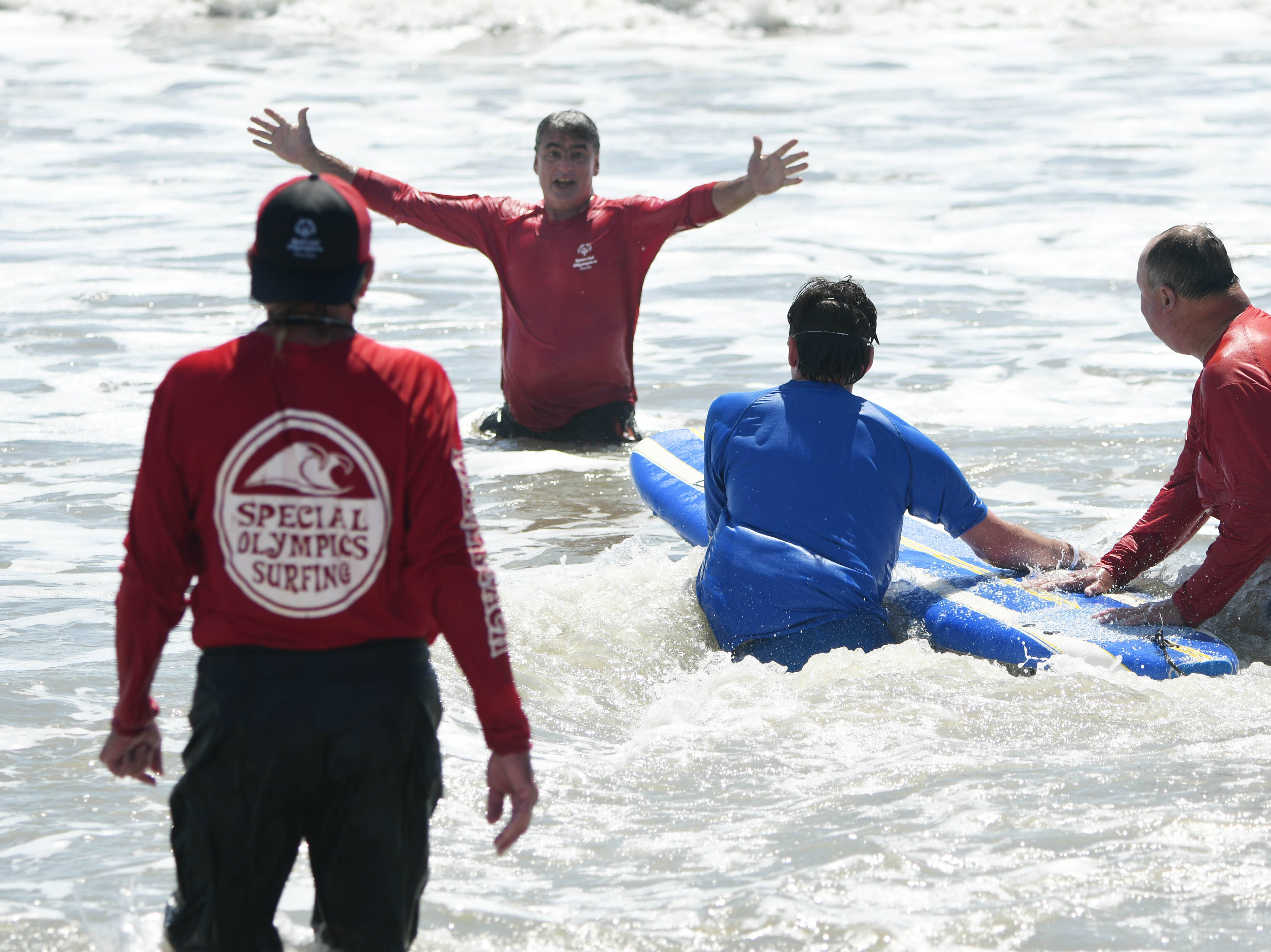 Bryand Padron ia encouraged and supported by his father Alfredo and other volunteers during the Special Olympics Florida spring surfing festival at Shepard Park.