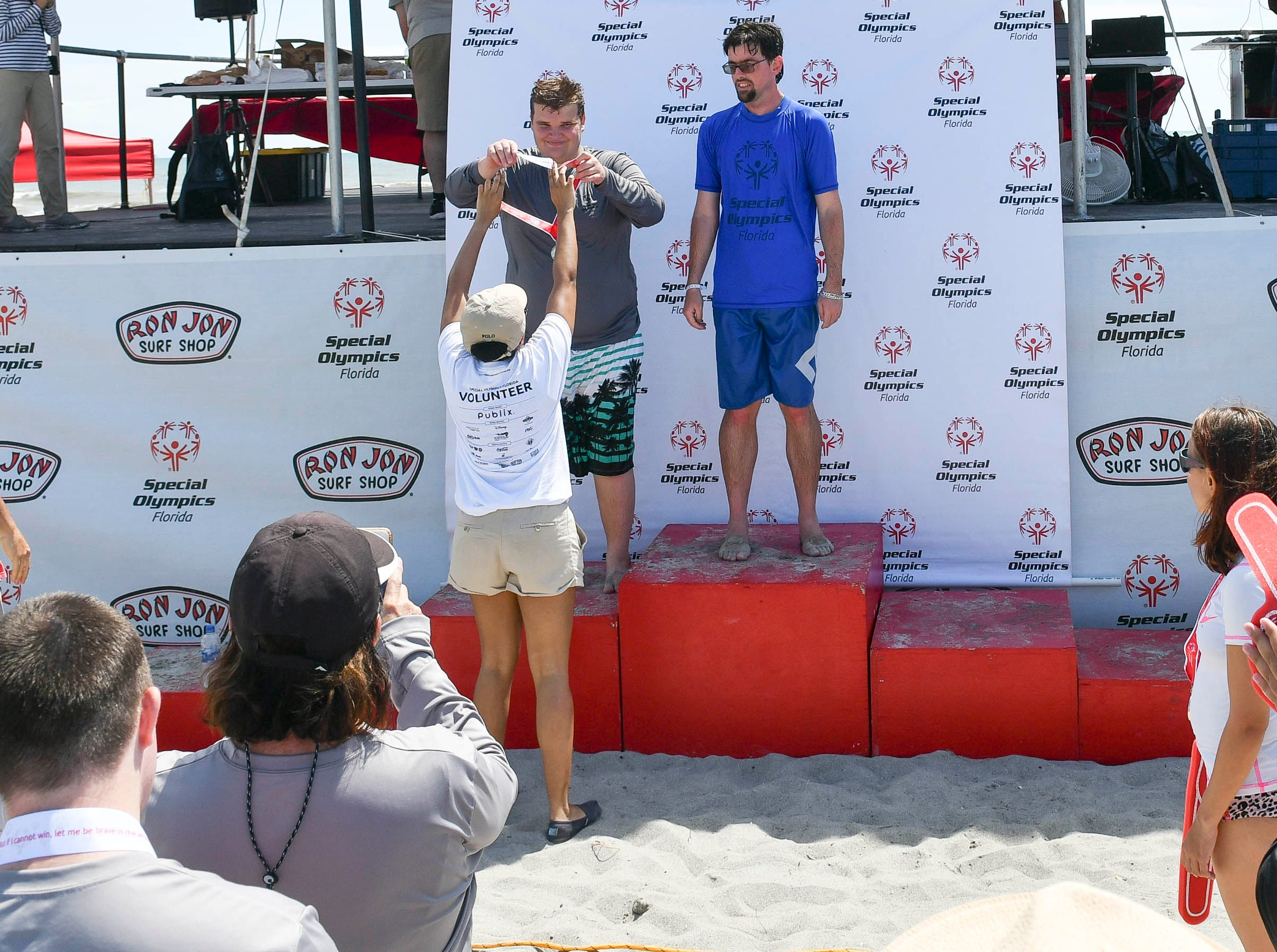 Bryan Padron and Jacob Nehus receive their medals during the Special Olympics Florida spring surfing festival at Shepard Park.