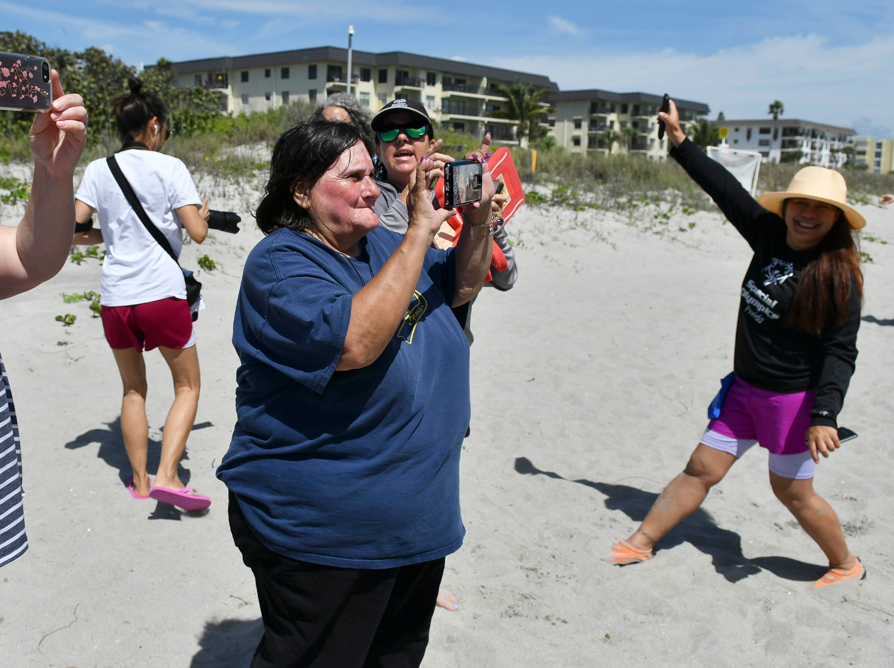 Parents and supporters take pictures during the medal presentation at the Special Olympic spring surfing festival.
