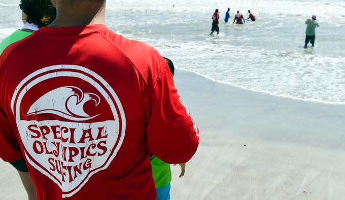 Spectators and supporters watch the surfing action during the Special Olympics Florida spring surfing festival at Shepard Park.
