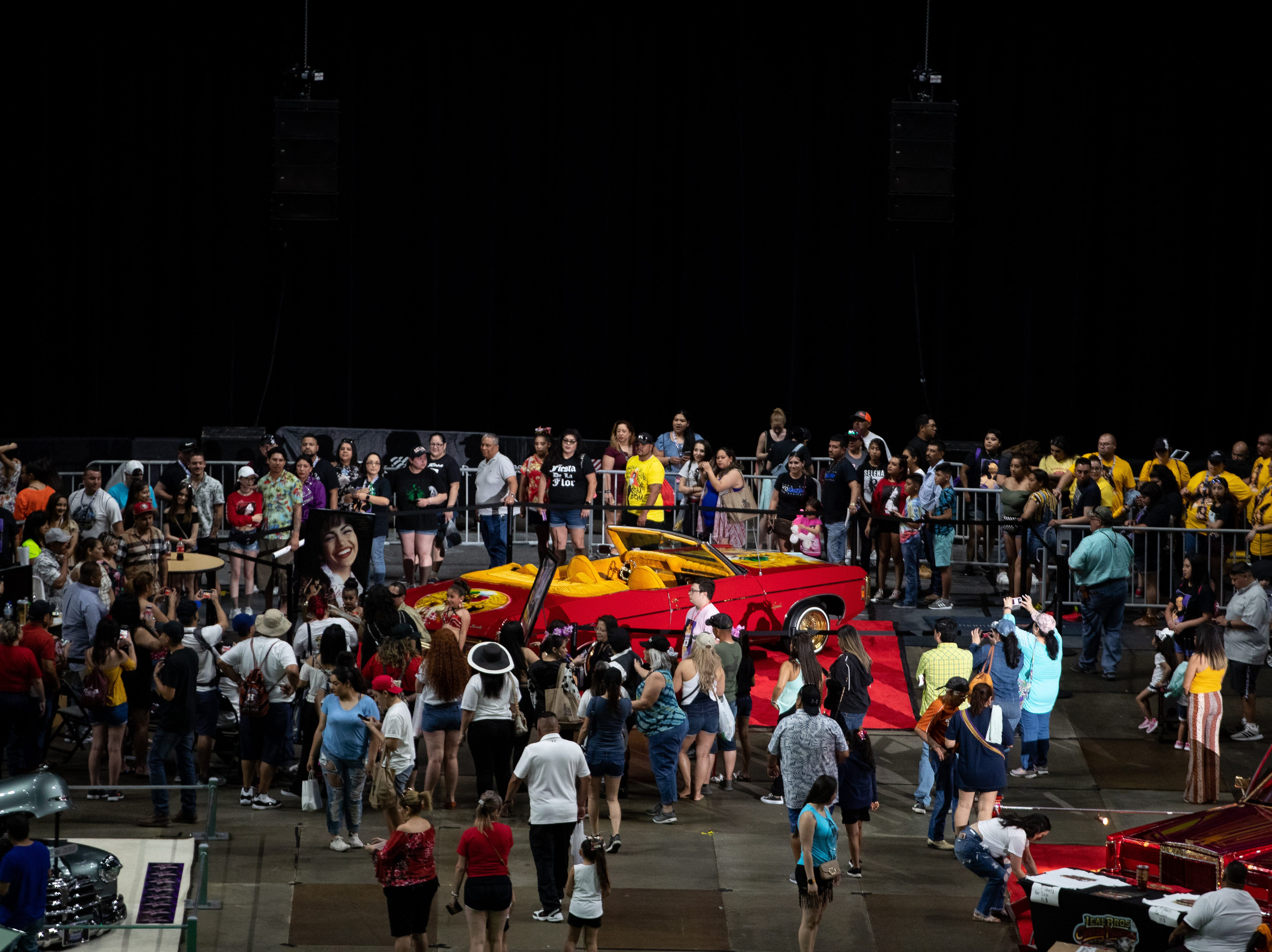 """People wait inline to take a photo with the """"Anything for the Selenas"""" car during the Lowrider Extravaganza at the American Bank Center on the second day of Fiesta de la Flor on Saturday, April 13, 2019."""