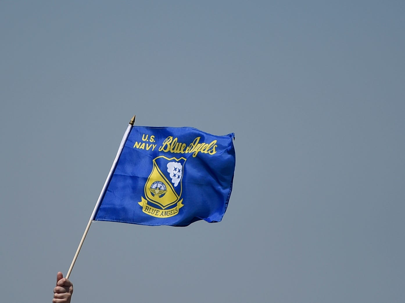A child holds a Blue Angels flag during the Wings Over South Texas Air Show, Saturday, April 13, 2019, at NAS Corpus Christi.