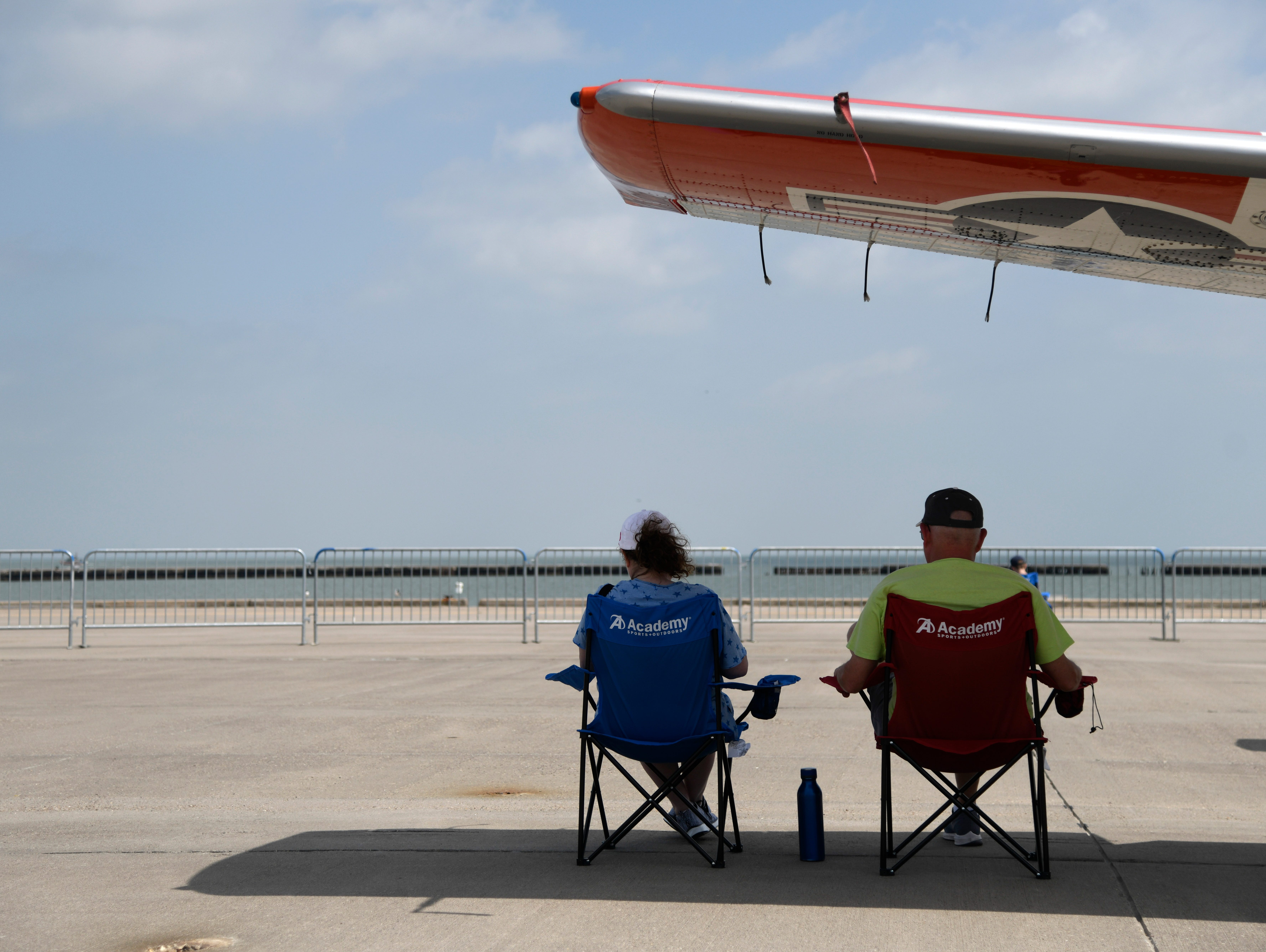 A couple finds shade under an airplane wing before the Wings Over South Texas Air Show, Saturday, April 13, 2019, at NAS Corpus Christi.