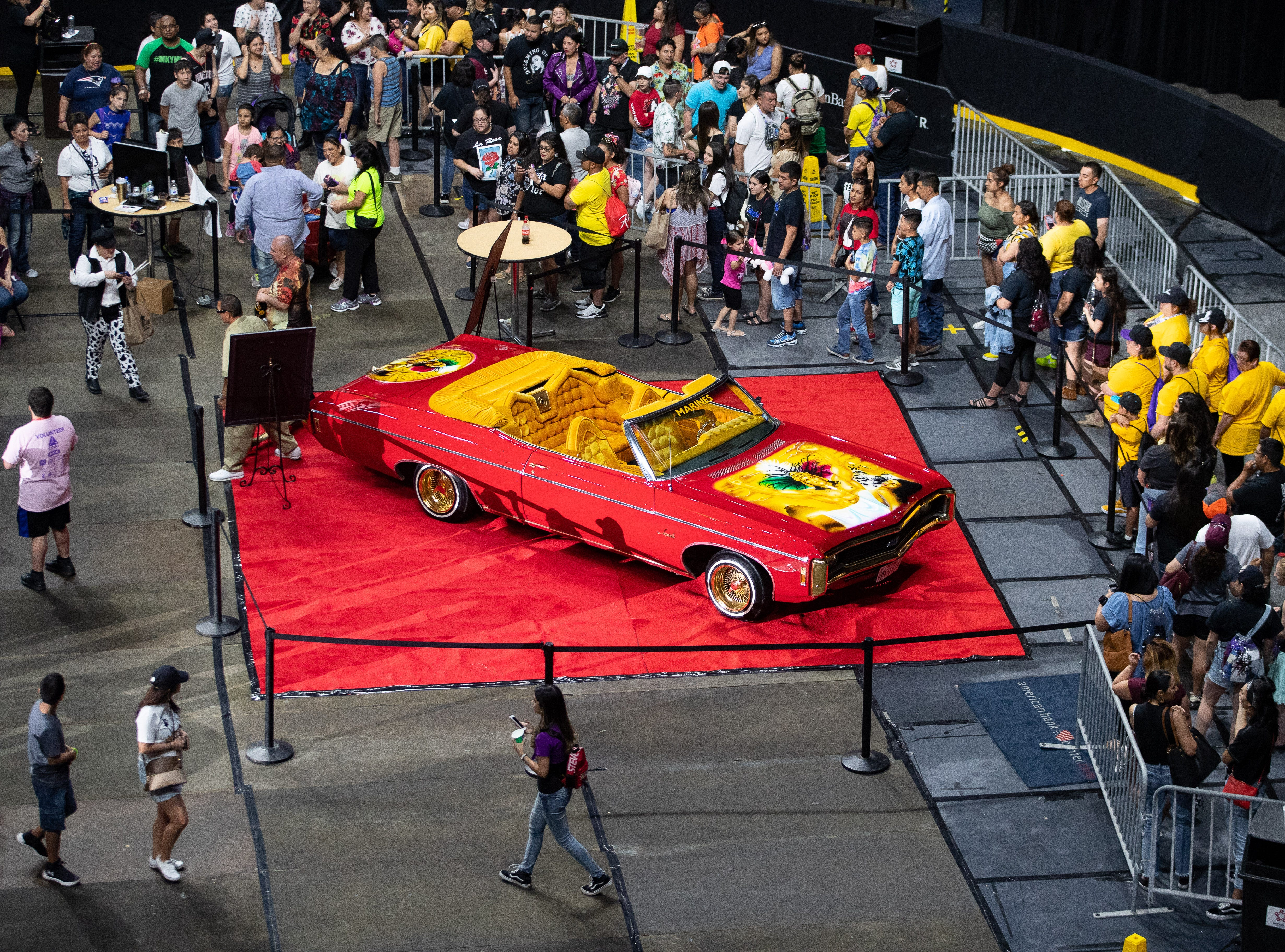 """People wait inline to take a photo with the """"Any thing for the Selenas"""" car during the Lowrider Extravaganza at the American bank center on the second say of Fiesta de la Flor on Saturday, April 13, 2019."""