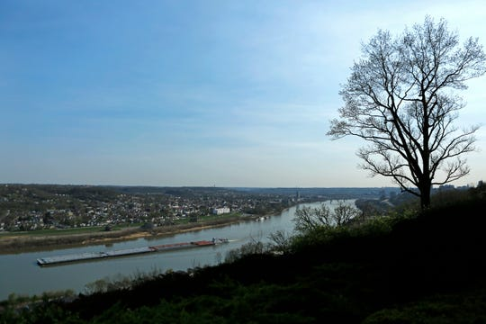 A cargo barge travels up the Ohio River, seen from an overlook in the East Walnut Hills neighborhood of Cincinnati on Wednesday, April 10, 2019.