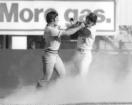 Pete Rose, left, swings at New York Mets shortstop Bud Harrelson after Rose failed to break up a double play in Game 3 of the 1973 National League Championship series. Both benches emptied in the ensuing brawl.