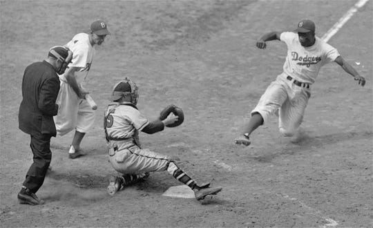 Jackie Robinson, Dodgers' second baseman, steals home plate successfully as Braves' catcher Bill Salkeld is thrown off-balance on pitcher Bill Voiselle's throw to the plate during the fifth inning of a Boston-Brooklyn game at Ebbets Field, New York, on August 22, 1948.