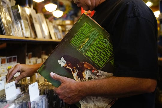 "Jamie Hartinger with a Herb Alpert album at Record Store Day at Shake It Records, April 13, 2019. When asked why this particular album, Hartinger pointed to the cover. ""The girl! It's classic Herb."""