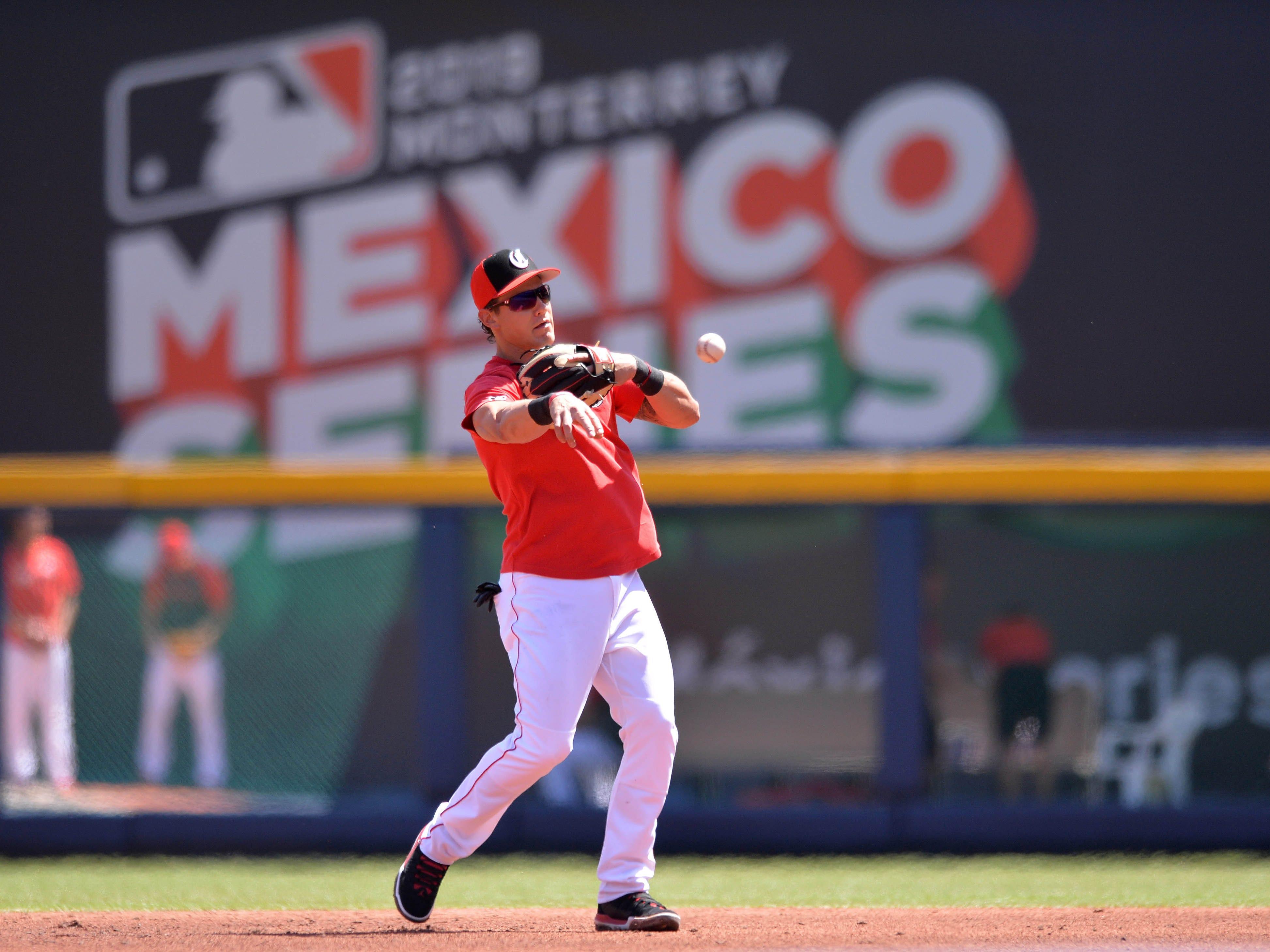 Cincinnati Reds Derek Dietrich throws in the infield before the game against the St. Louis Cardinals at Estadio de Beisbol Monterrey.
