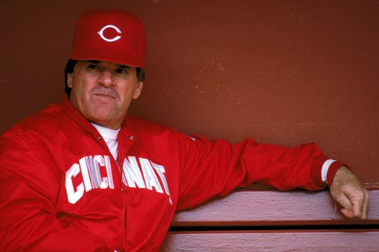 Then-Reds Manager Pete Rose sits in the dugout during a game in 1989.