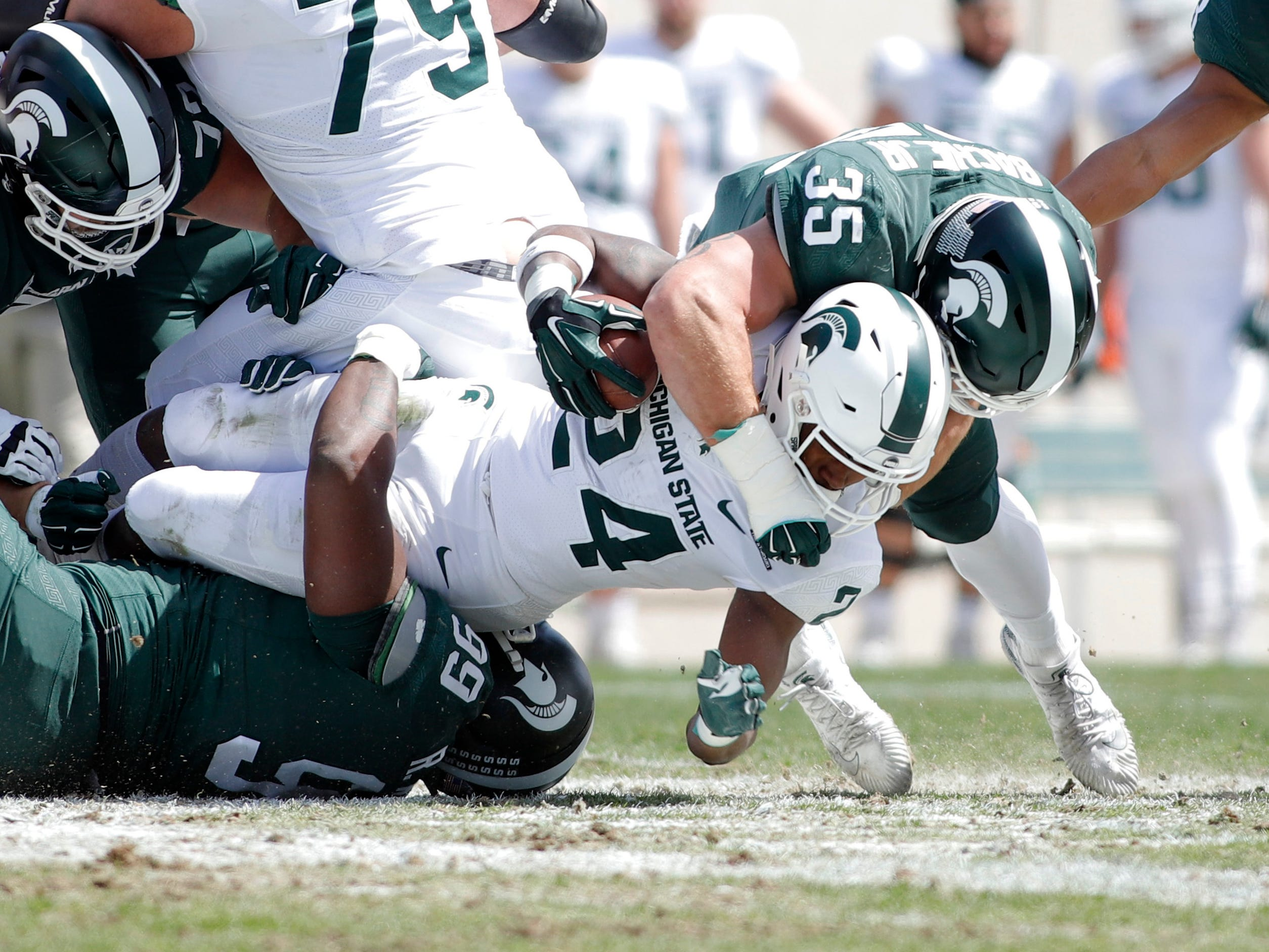Michigan State's Joe Bachie, right, and Raequan Williams, bottom, tackle Elijah Collins during a spring scrimmage Saturday, April 13, 2019, in East Lansing.