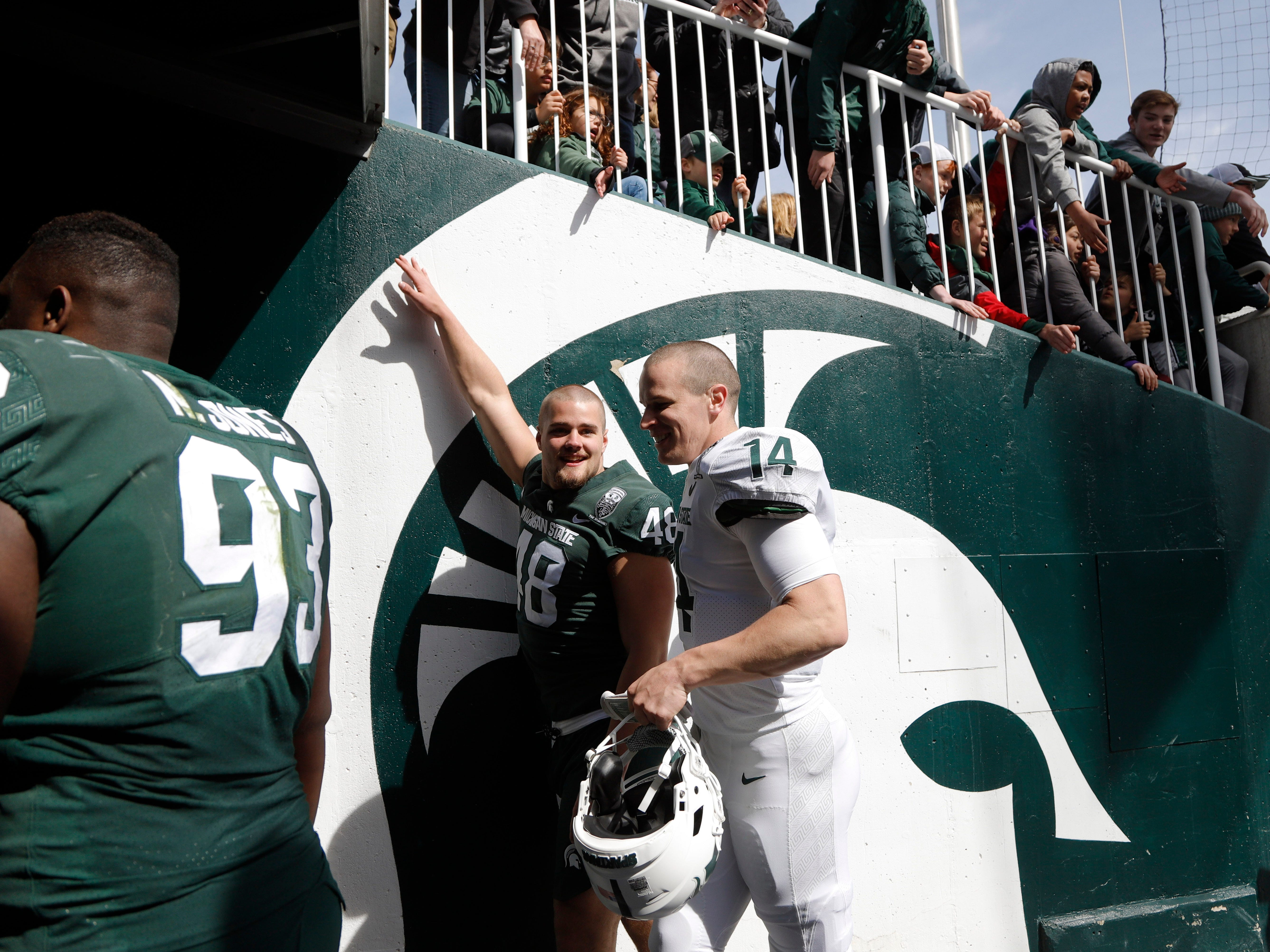 Michigan State quarterback Brian Lewerke, right, and defensive end Kenny Willekes (48) leave the field after their spring scrimmage Saturday, April 13, 2019, in East Lansing.