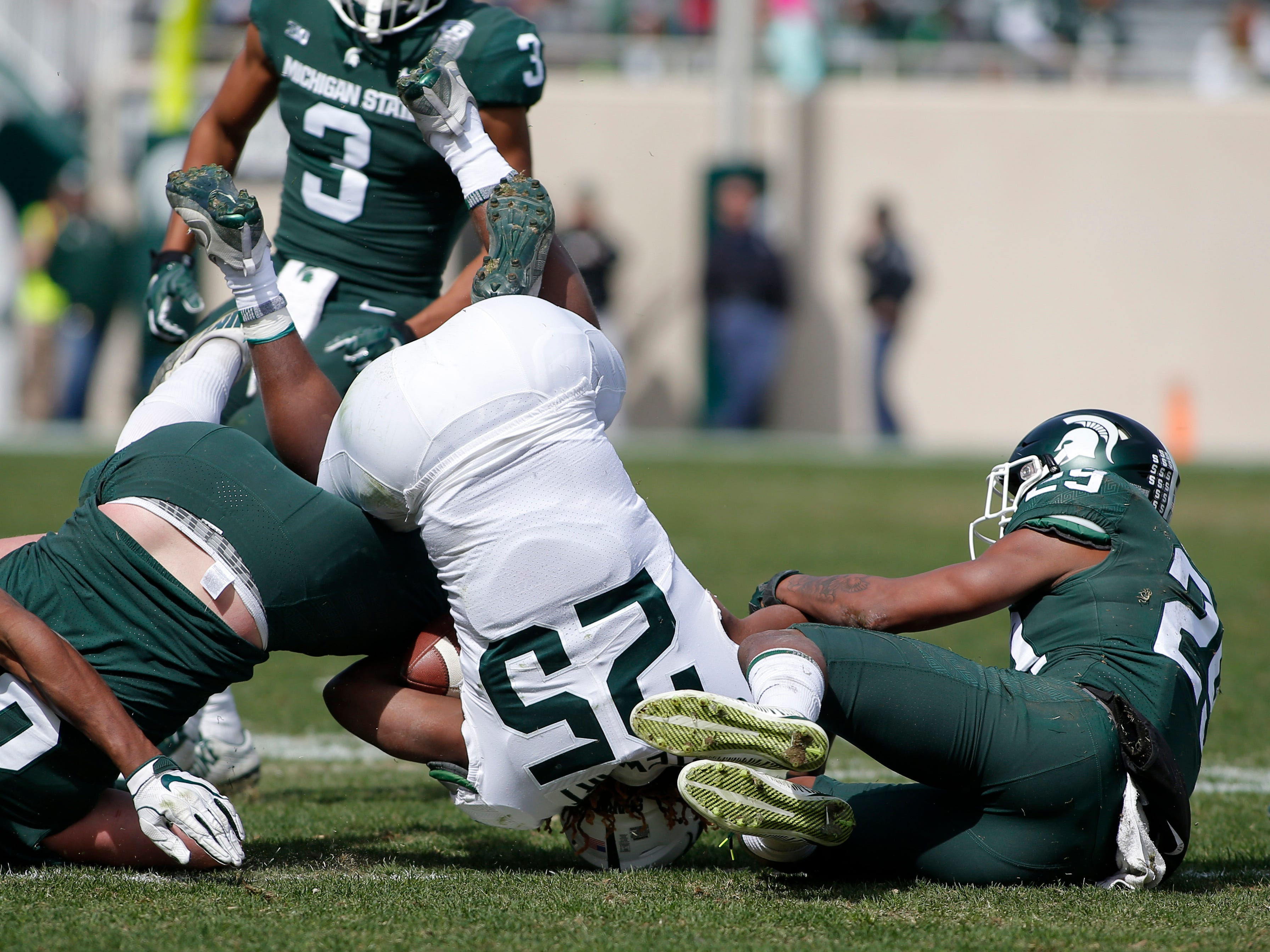 Michigan State's Darrell Stewart Jr. (25) is upended by Shakur Brown (29), Brandon Bouyer-Randle (26) and Drew Beesley during a spring scrimmage Saturday, April 13, 2019, in East Lansing.