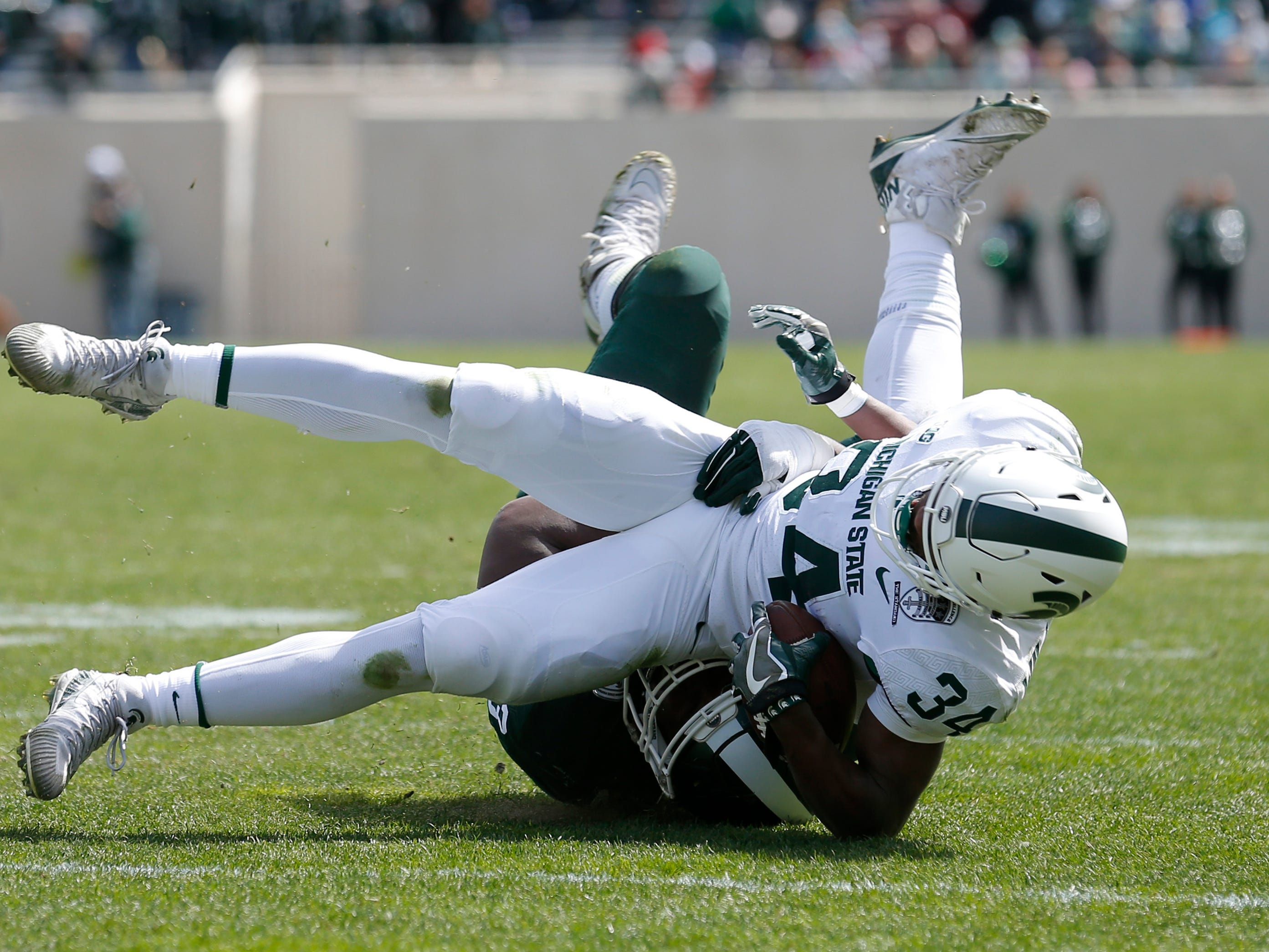 Michigan State's Anthony Williams is tackled by Naquan Jones during a spring scrimmage Saturday, April 13, 2019, in East Lansing.