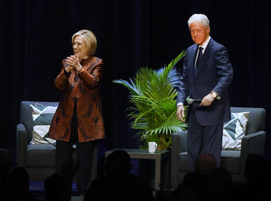 President Bill Clinton and former Secretary of State Hillary Rodham Clinton make their way onto the stage to take part in a series of conversations across 13 cities, making a stop at the Fox Theater in Detroit Michigan on April 12, 2019.