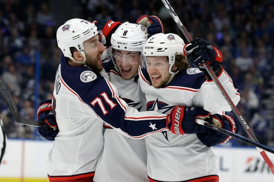 Columbus Blue Jackets defenseman Zach Werenski (8) celebrates his goal against the Lightning with left wing Nick Foligno (71) and left wing Artemi Panarin (9) during the first period on Friday.
