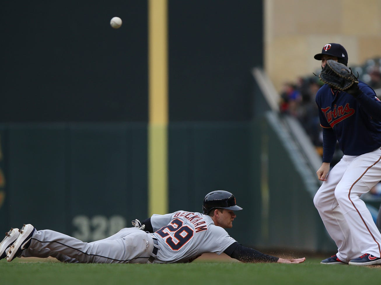 Detroit Tigers' Gordon Beckham slides back to first base against Minnesota Twins' C.J. Cron in the ninth inning.