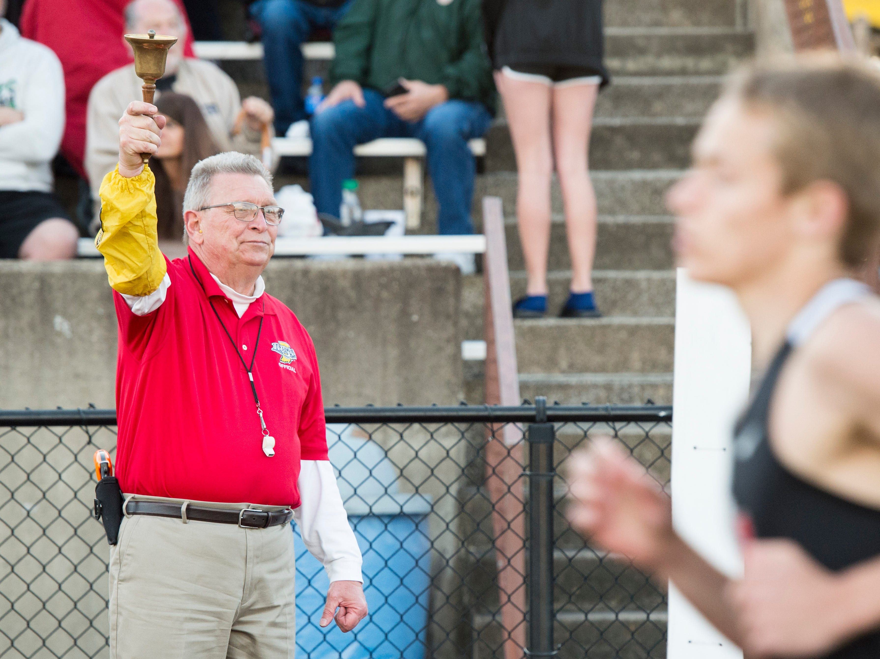 Official Ron Schell rings the bell for the boys 800m run during 2019 City Track and Field meet at Central High School Friday, April 12, 2019.