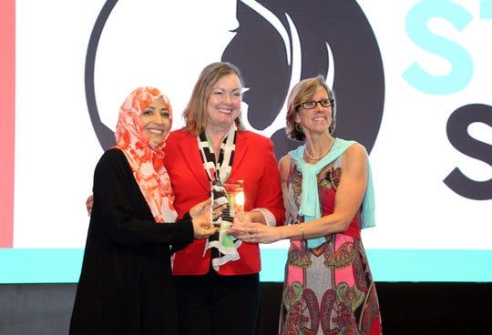 Provost Sally McRorie accepts PeaceJam's inaugural Innovative Leadership Award from Nobel Peace Prize laureate Tawakkol Karman and PeaceJam Executive Director Kate Cumbo.