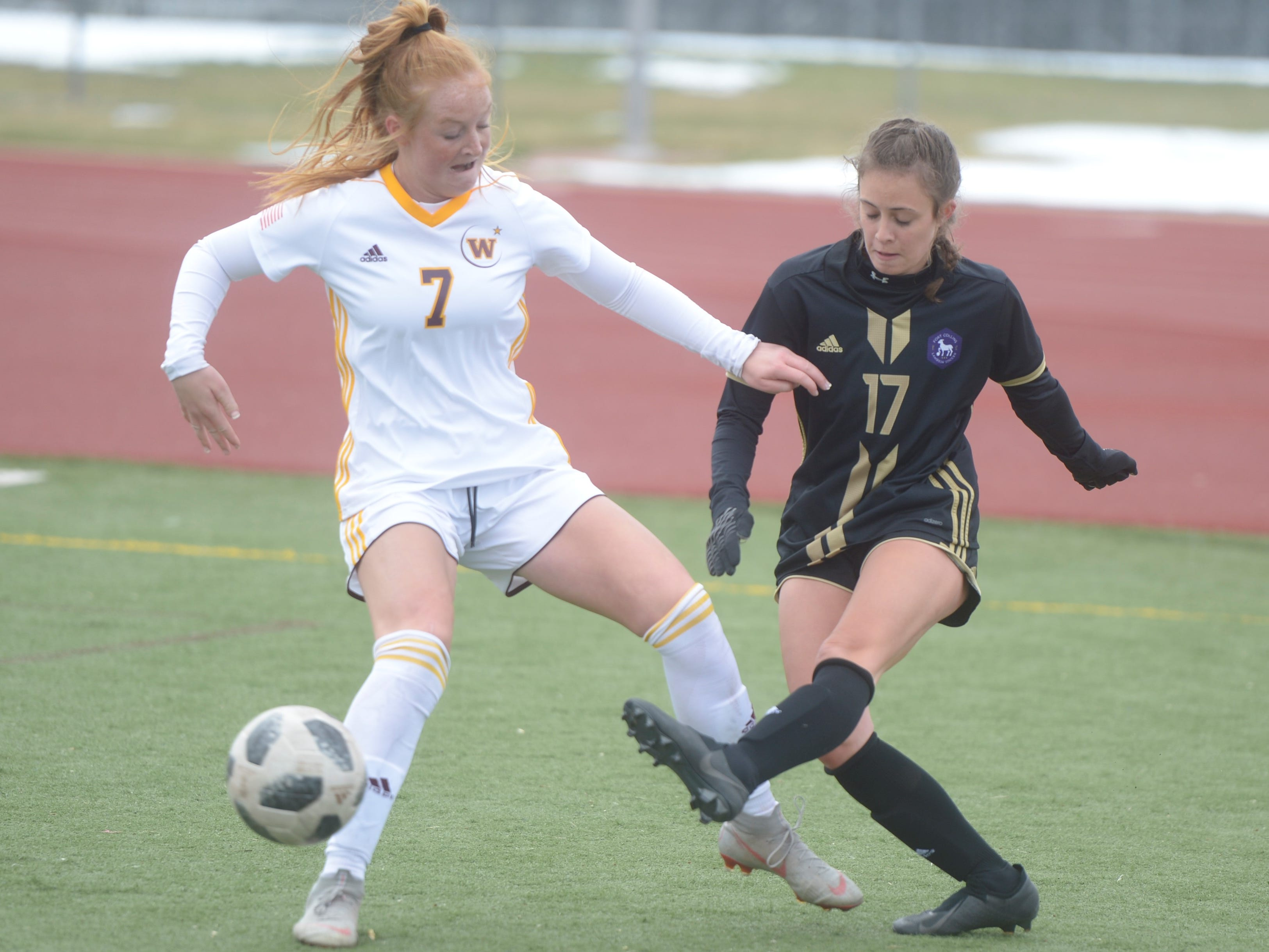 Fort Collins soccer player Stella Straubing, right, passes the ball past Windsor's Halle Moody during a game Saturday, April 13, 2019 at Fossil Ridge. Windsor won 3-0.