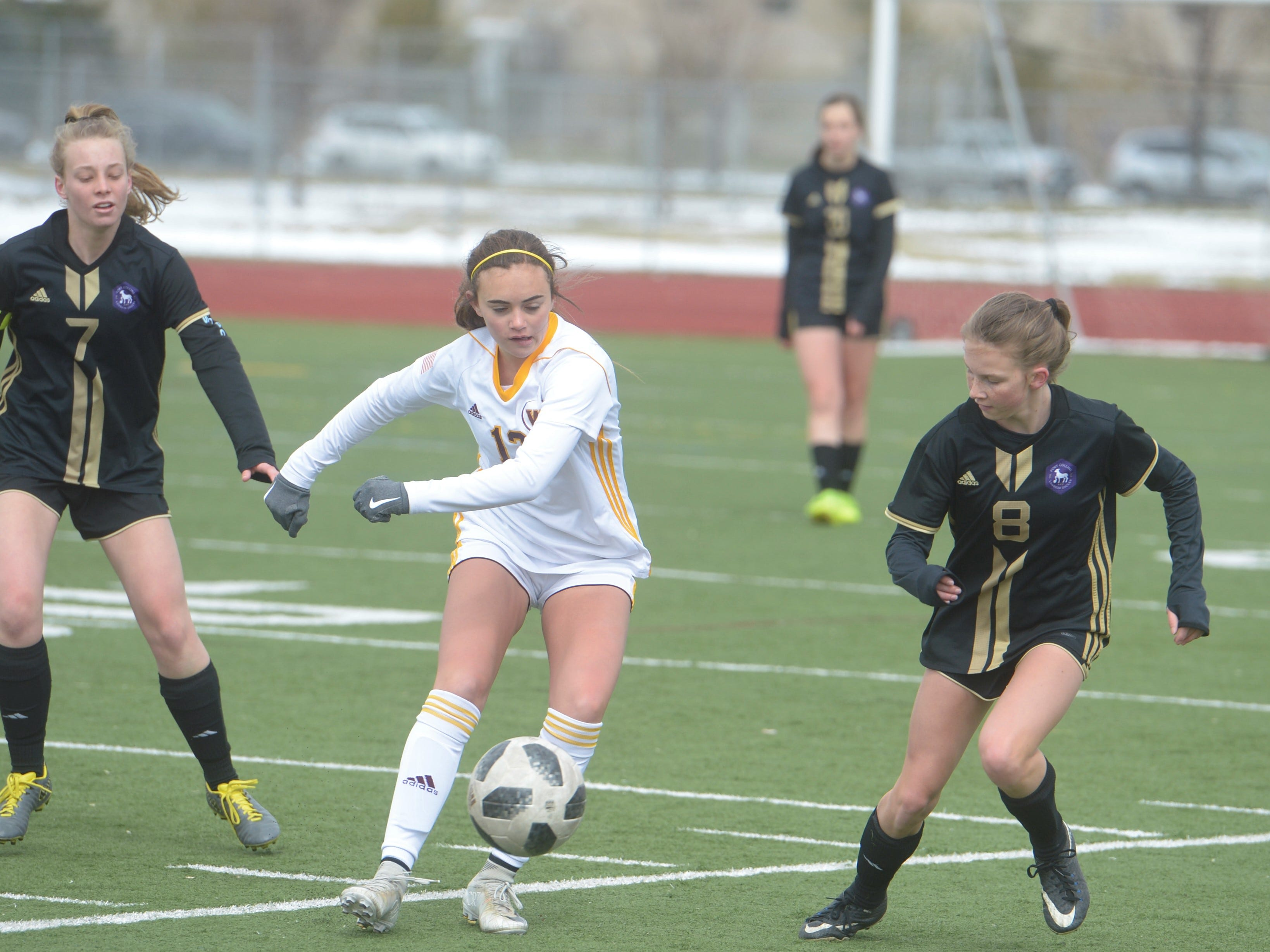 Windsor soccer player Jojo Hardy, middle, passes the ball past Fort Collins defenders during a game Saturday, April 13, 2019 at Fossil Ridge. Windsor won 3-0.