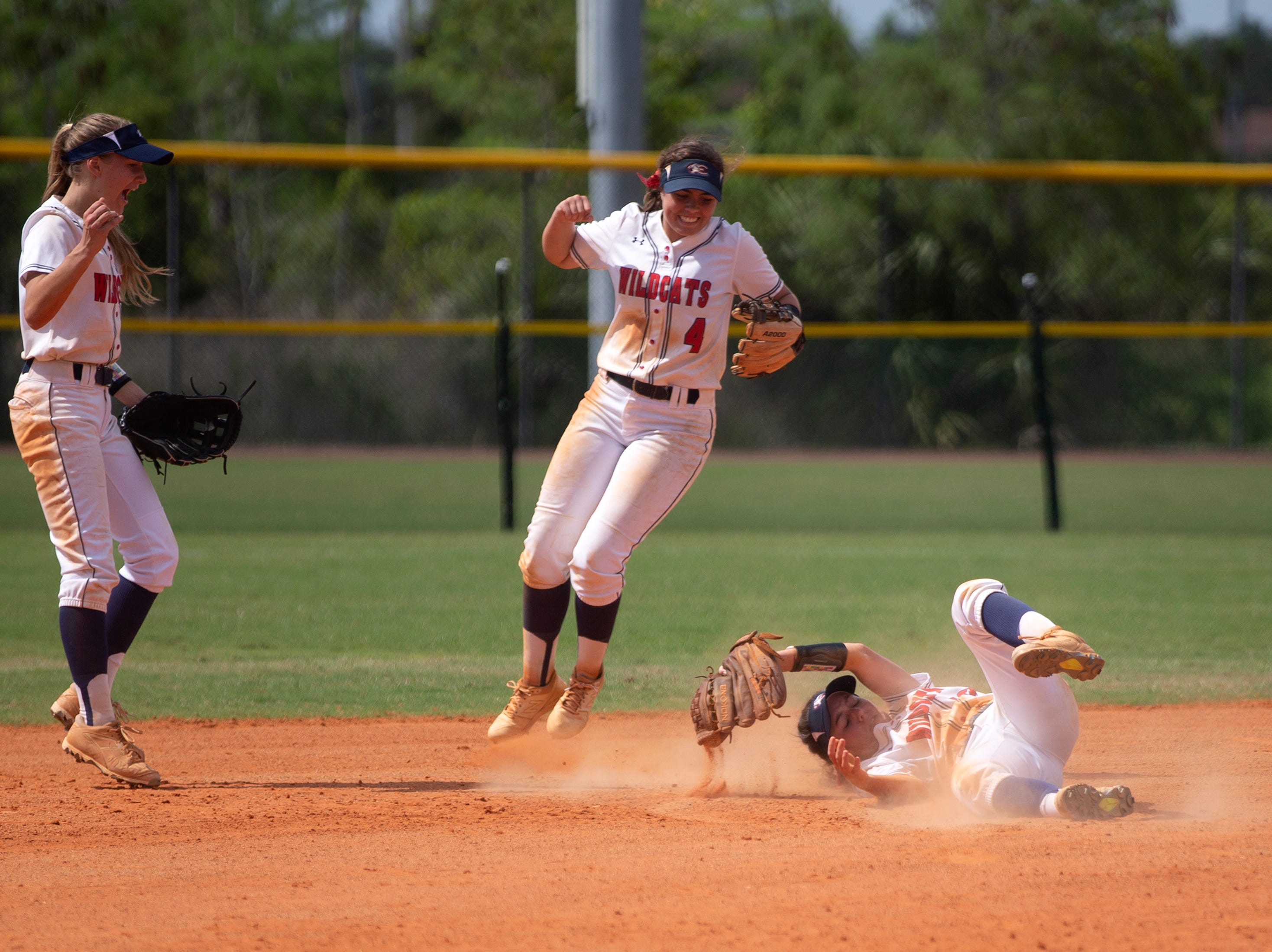 Estero's Grace Horty, left, and Anna Raybuck, celebrate after teammate Chelsea Dumas makes an infield catch for an out against Dural Academy during the Longshore Memorial softball tournament, Saturday, April 13, 2019, at North Collier Regional Park in North Naples.
