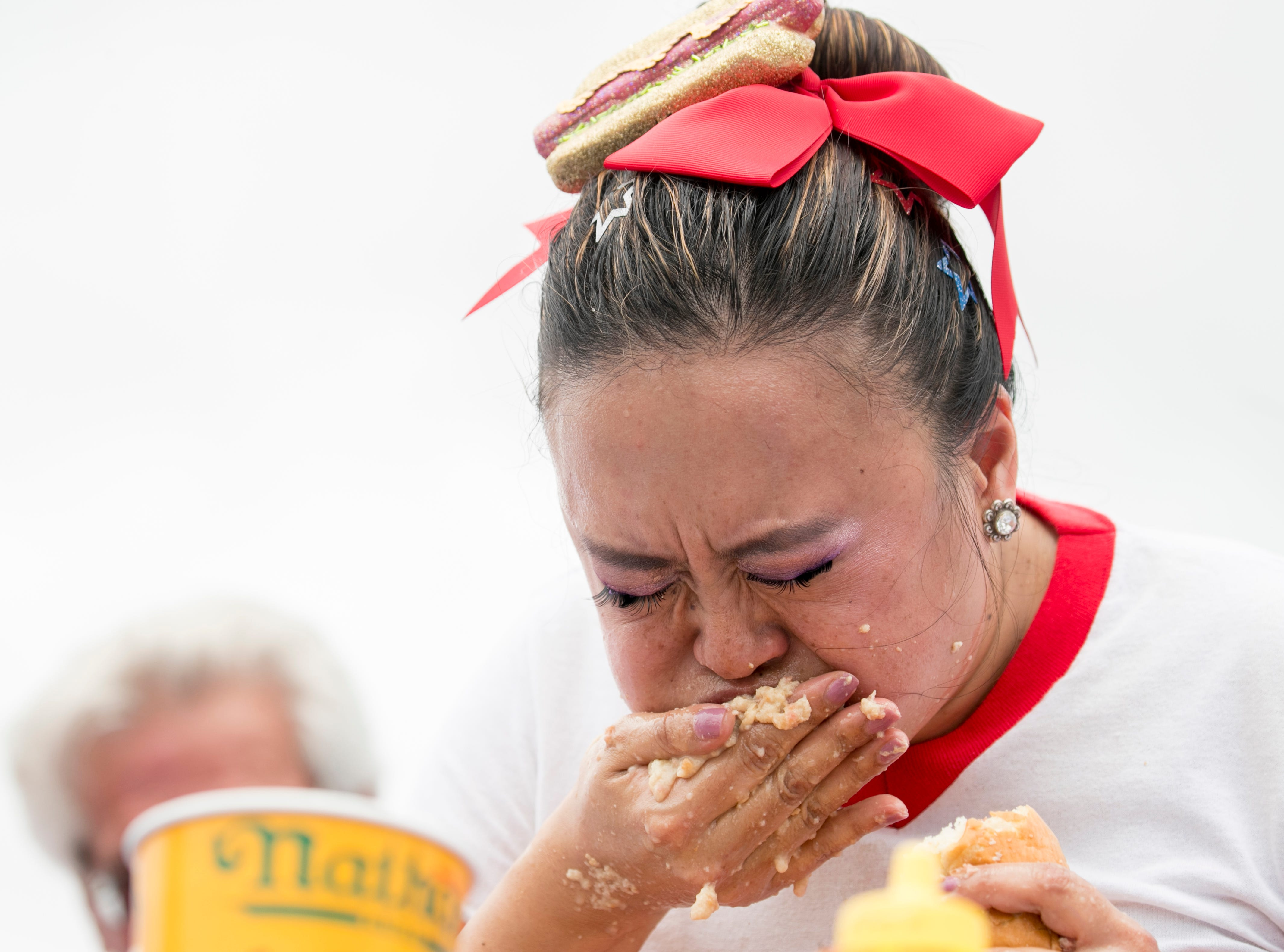 Mary Bowers eats in the Nathan's Famous Hot Dog Eating Contest on Saturday, April 13, 2019, in Cape Coral. Bowers was the first place woman and qualified to compete in the 2019 Nathan's Famous Fourth of July International Hot Dog-Eating Contest.