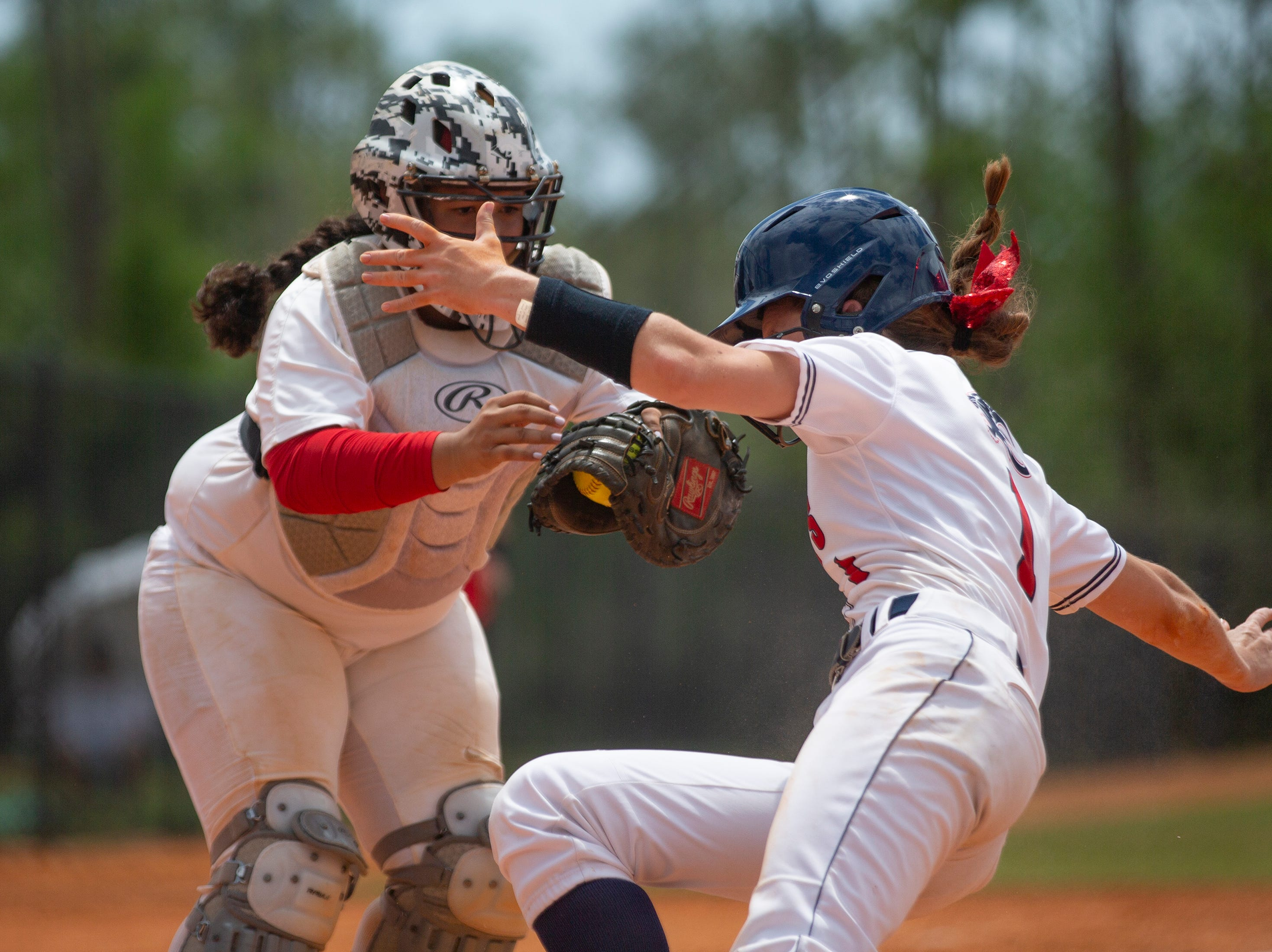 Doral Academy's Amanda Ramirez stops Estero's Tyler Olive from scoring a run during the third place game at the Longshore Memorial softball tournament, Saturday, April 13, 2019, at North Collier Regional Park in North Naples.