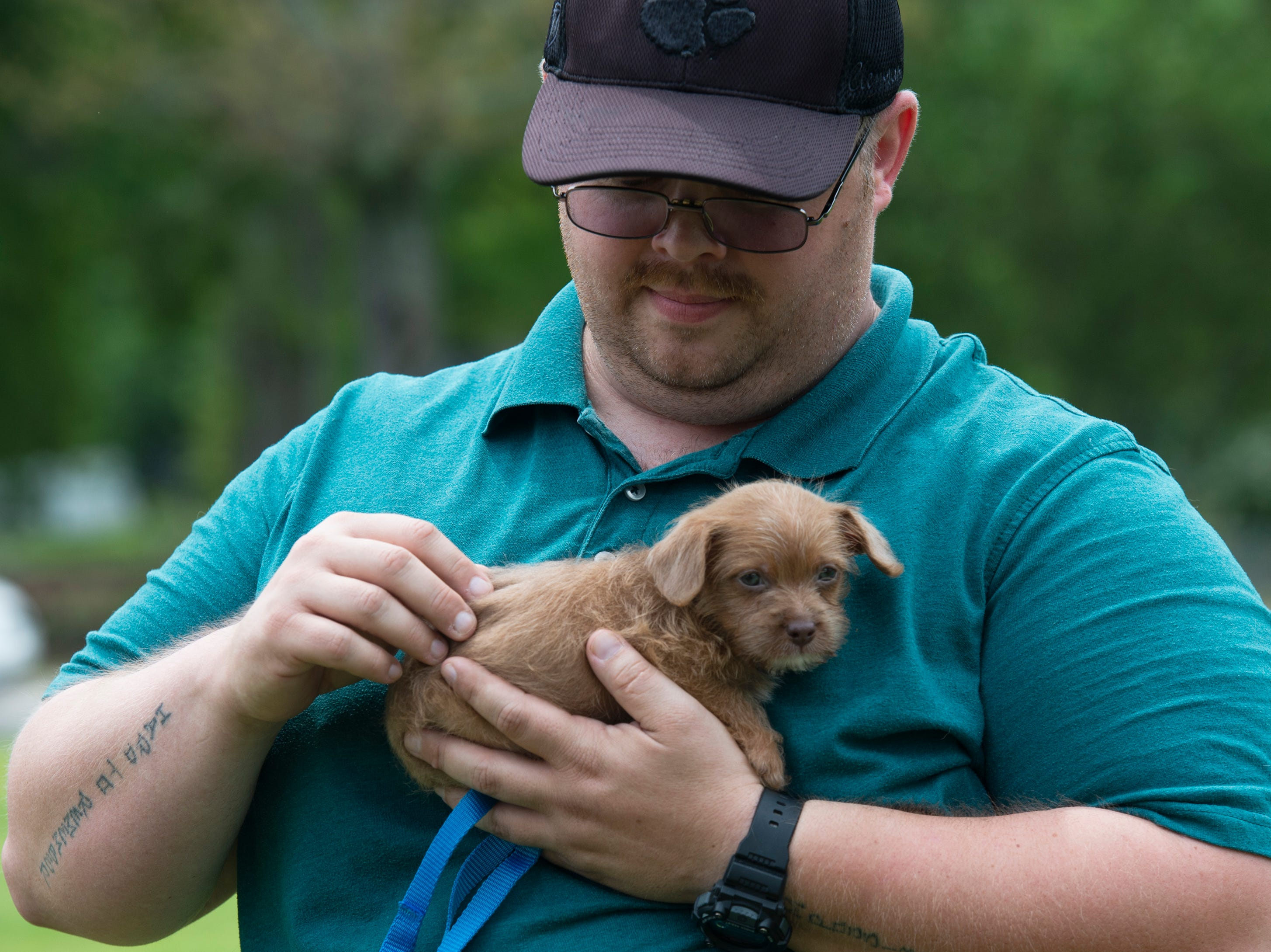 Warren Lanford, of Simpsonville, carries his puppy, Peanut, during Paws for a Cause in Simpsonville City Park Saturday, April 13, 2019.