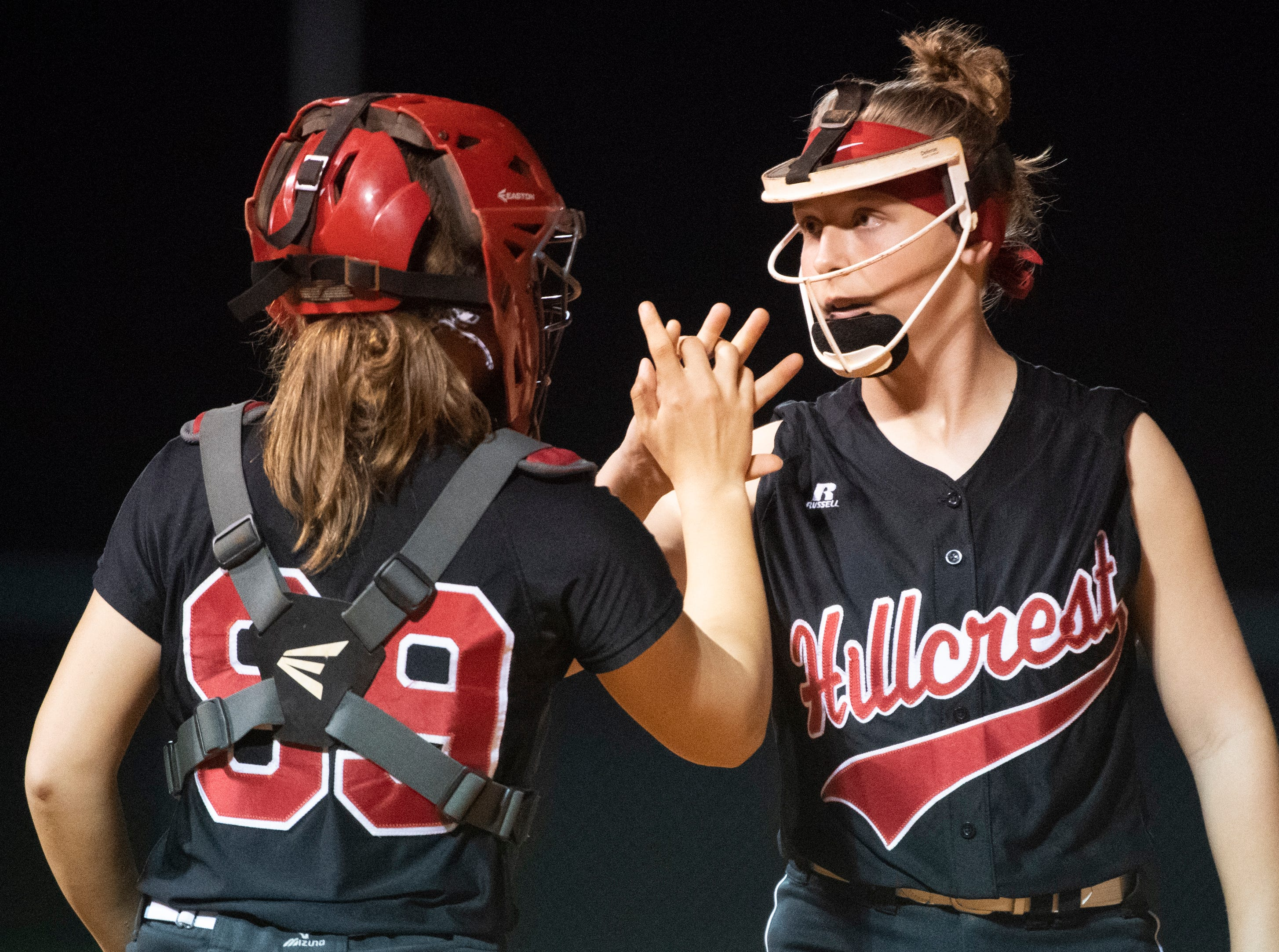 Hillcrest's pitcher Kristyn Ezzo (2) (right) and catcher Hannah Stevens (99) shake hands at the start of an inning during the game against Boiling Springs High School at Hillcrest Friday, April 12, 2019.