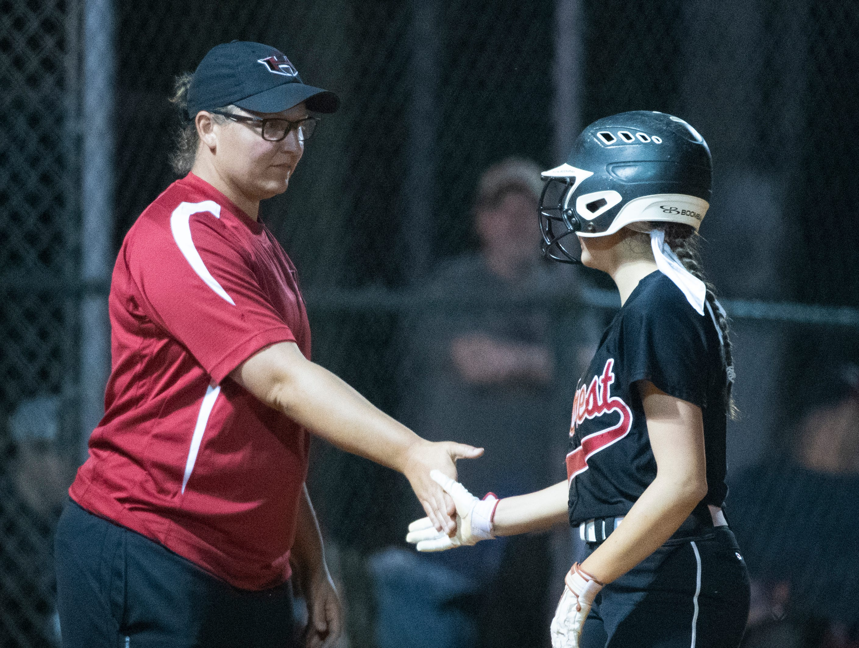 Hillcrest's Abby Willis (6) and coach Kristen Brust slap hands after Willis ran to third base during the game against Boiling Springs High School at Hillcrest Friday, April 12, 2019.